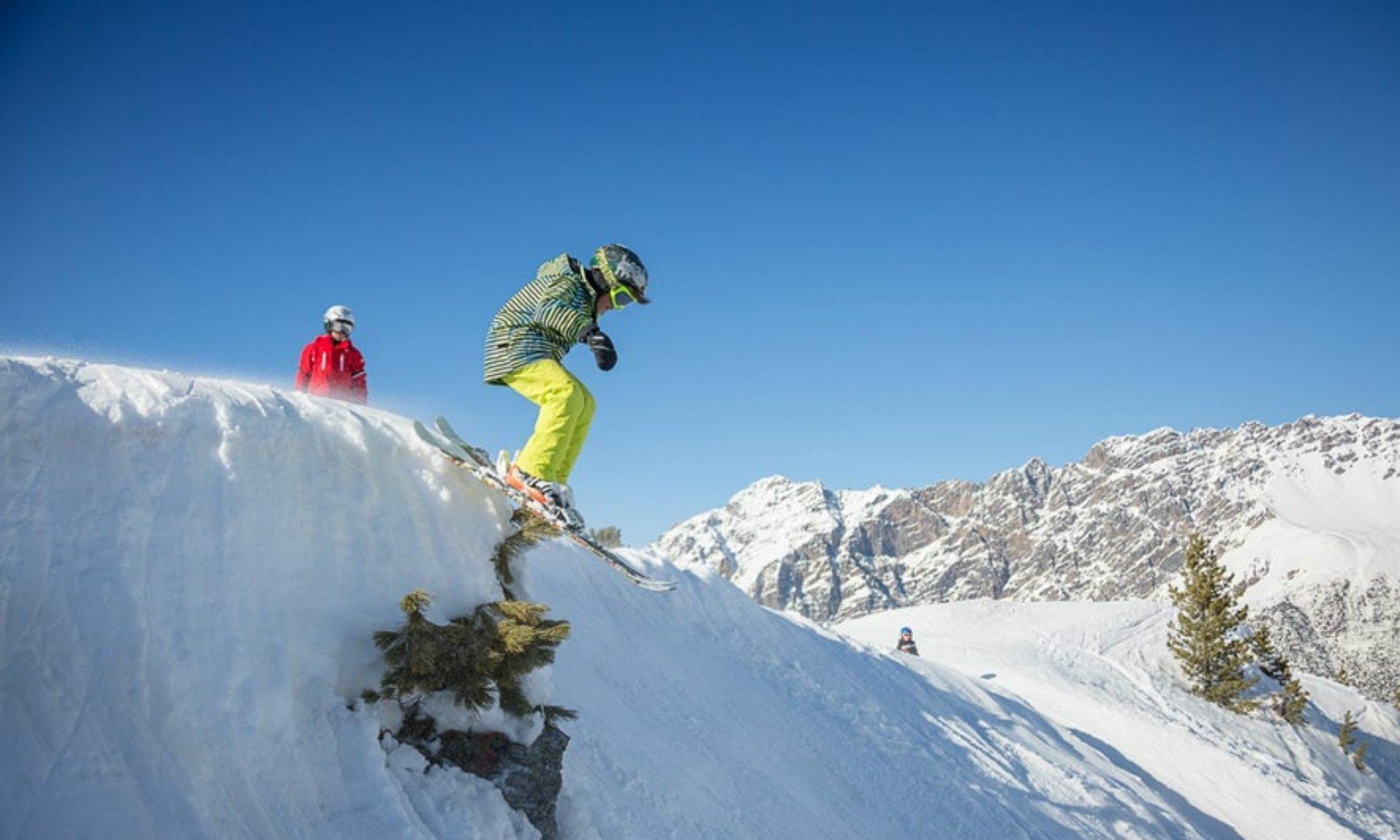 Un maestro di sci aiuta un adolescente ad imparare un trucco di freestyle.