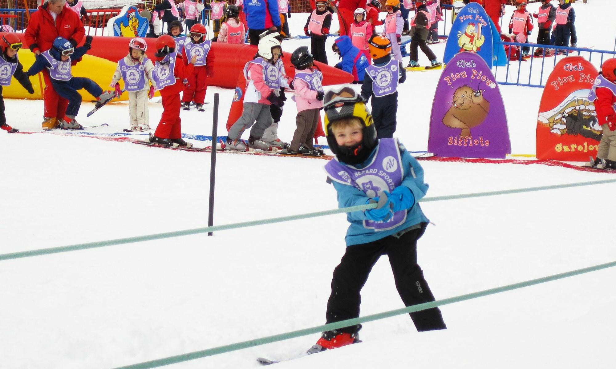Un jeune skieur utilise une télécorde dans un jardin d'enfants.