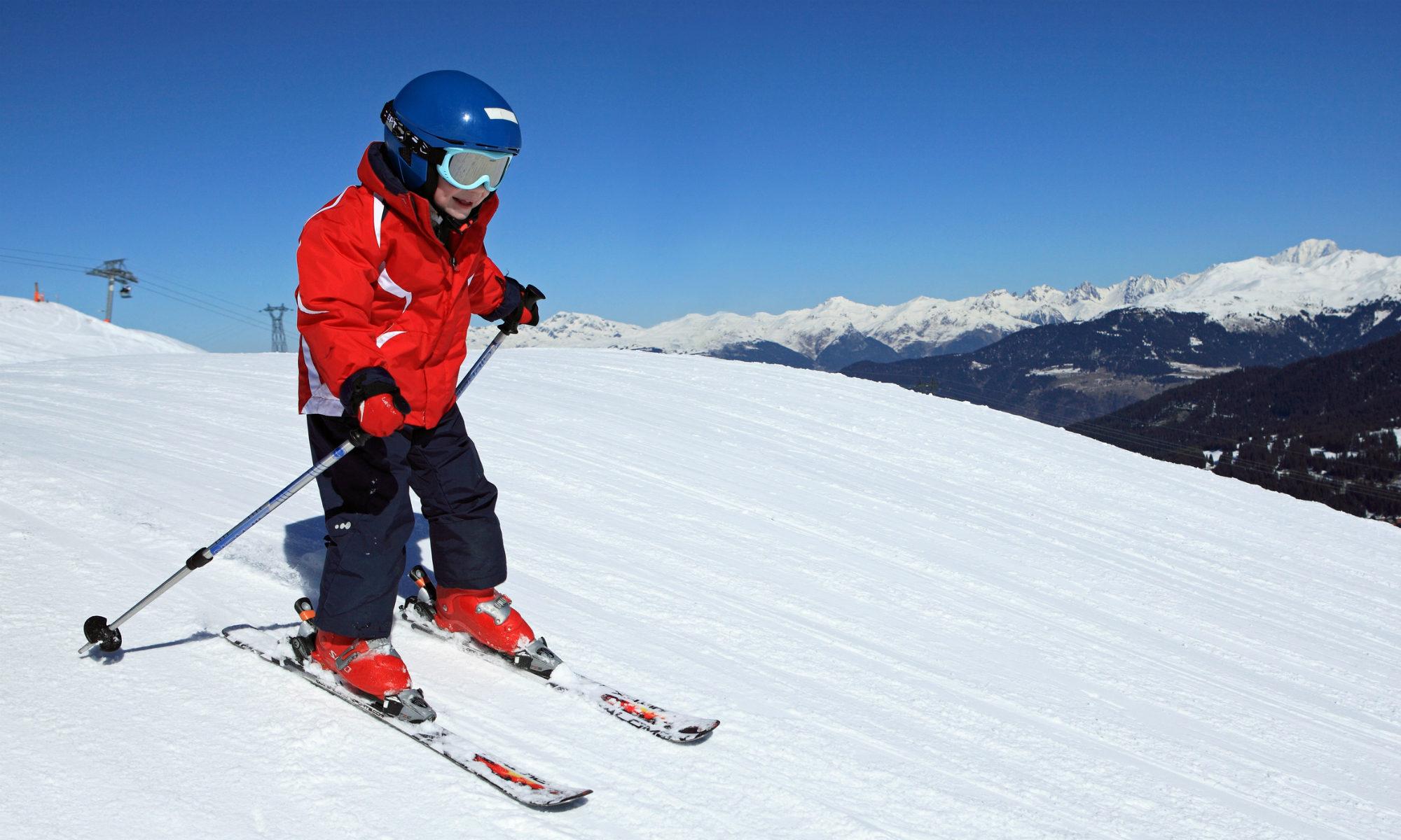 Un enfant skie sur une piste de difficulté moyenne.