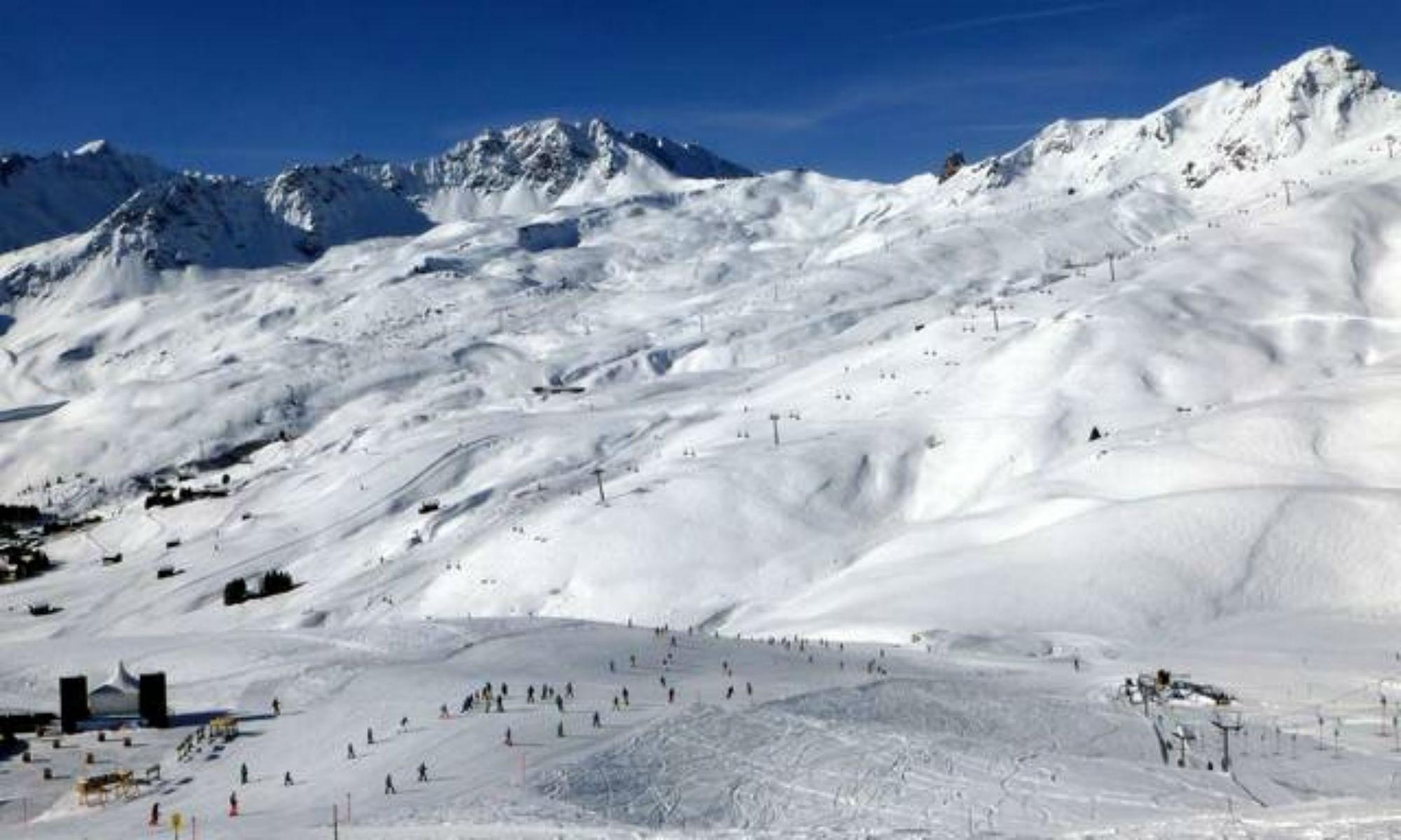 Tief verschneite Pisten im Skigebiet Arosa Lenzerheide bei sonnigem Wetter.