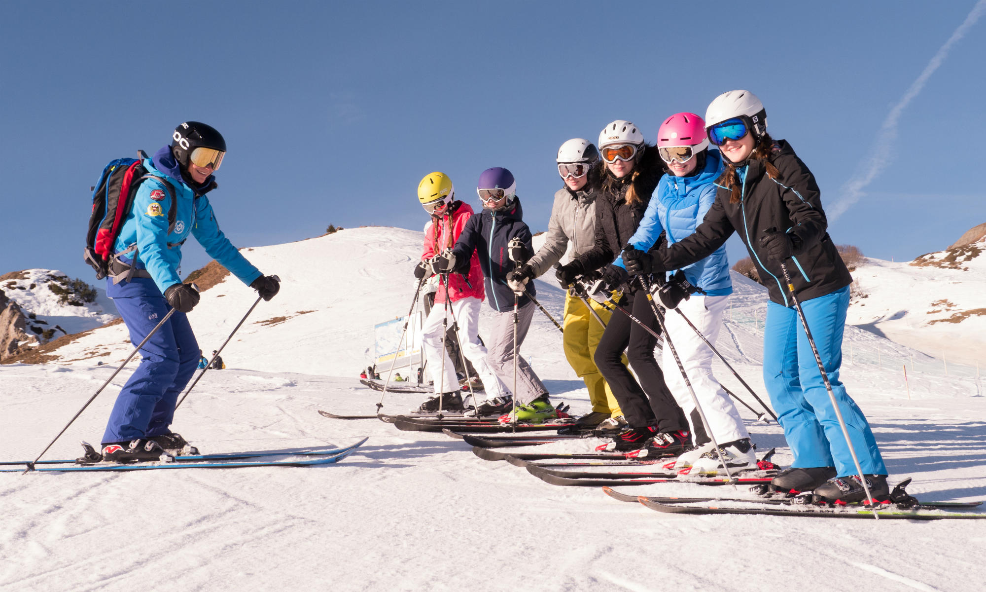 A group of teenagers on a sunny pist while skiing.