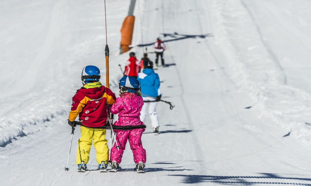 2 kids riding the drag lift in Going-Ellmau.