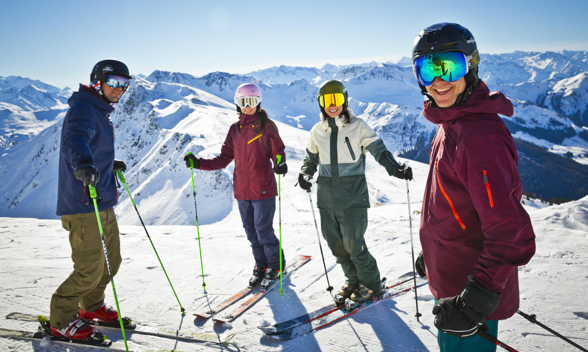 Young adults standing on a mountain peak in Saalbach-Hinterglemm and enjoying the view over the snowy surroundings.