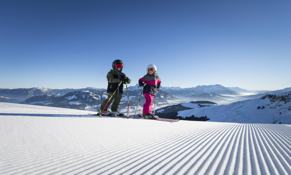 Children standing on a freshly groomed slope in front of a breathtaking mountain-background.