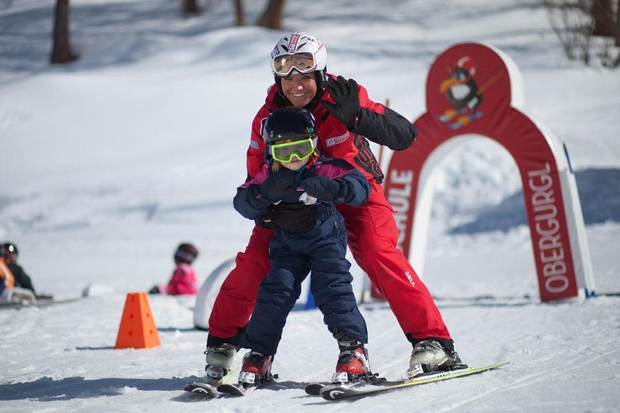 A Ski instructor and a child while practising the right skiing technique in a kids' area.