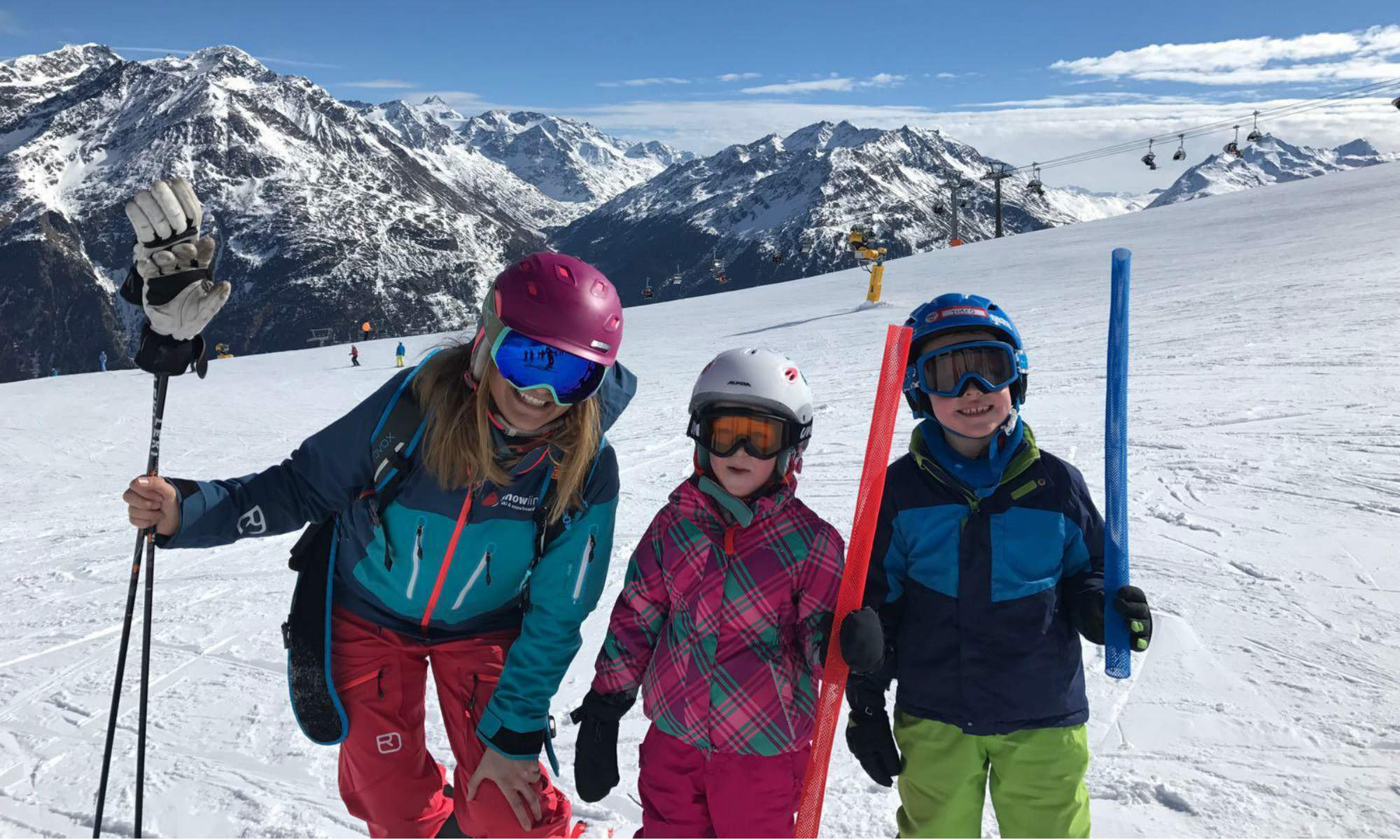 A ski instructor and two children are standing on a sunny slope in Obergurgl.