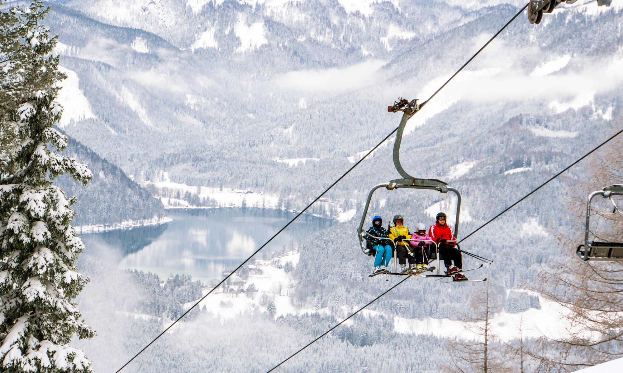 4 Skifahrer auf einem Sessellift im tief verschneiten Skigebiet Mariazell-Bürgeralpe.