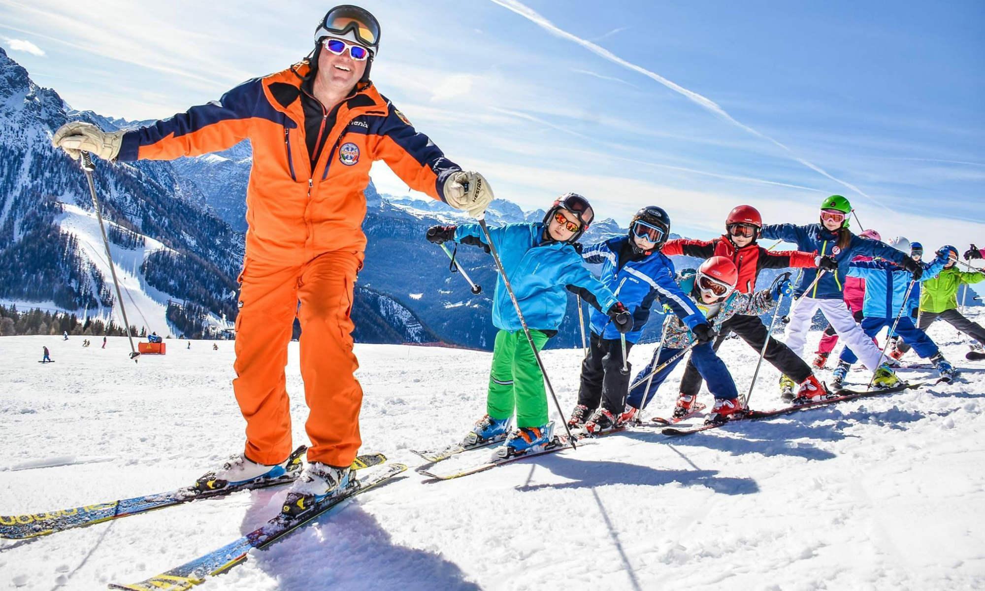 Skilehrer mit einer Gruppe von Kindern beim Üben der Skitechnik im Skigebiet Kronplatz.