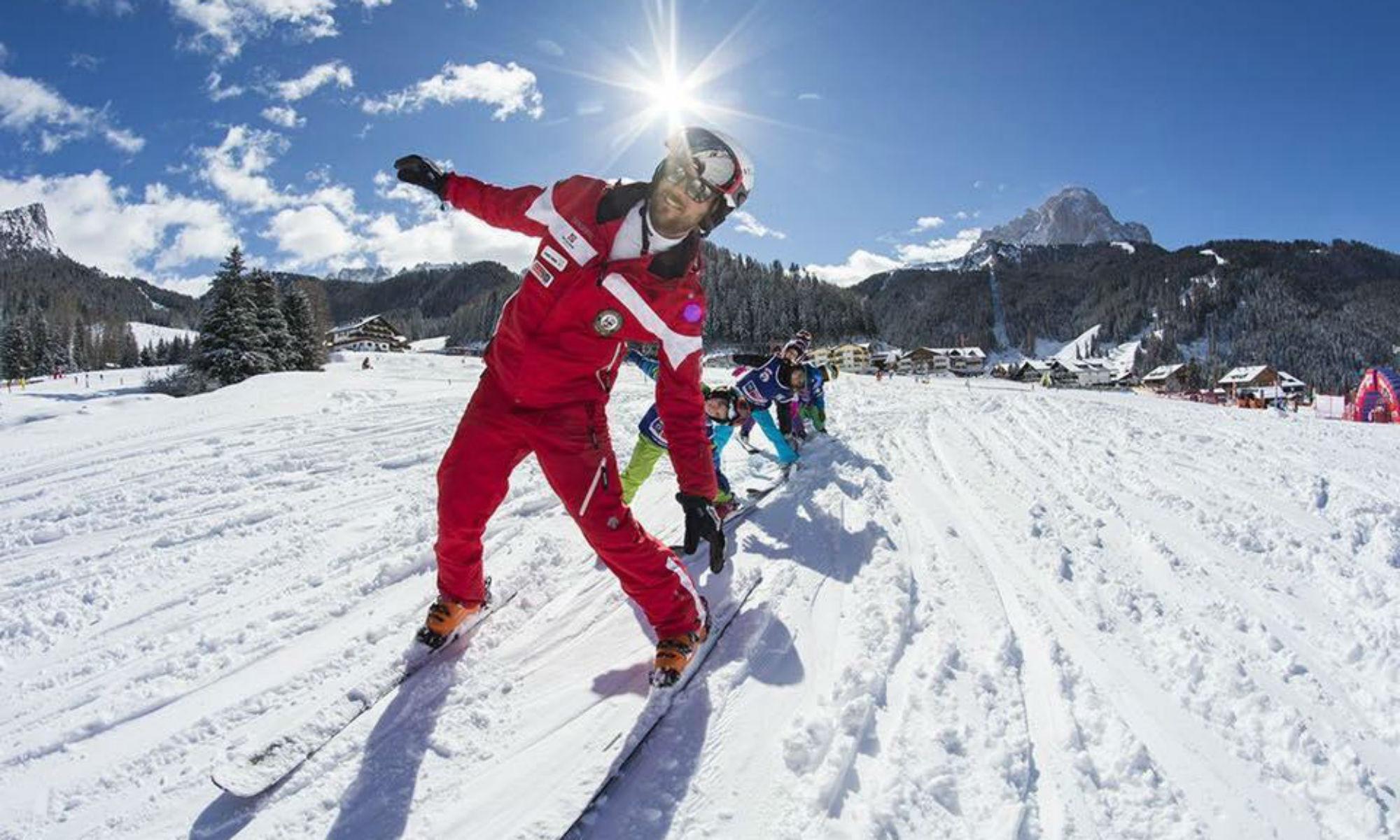 Skilehrer beim Skiunterricht mit mehreren Kindern auf einer sonnigen Piste im Skigebiet Wolkenstein.