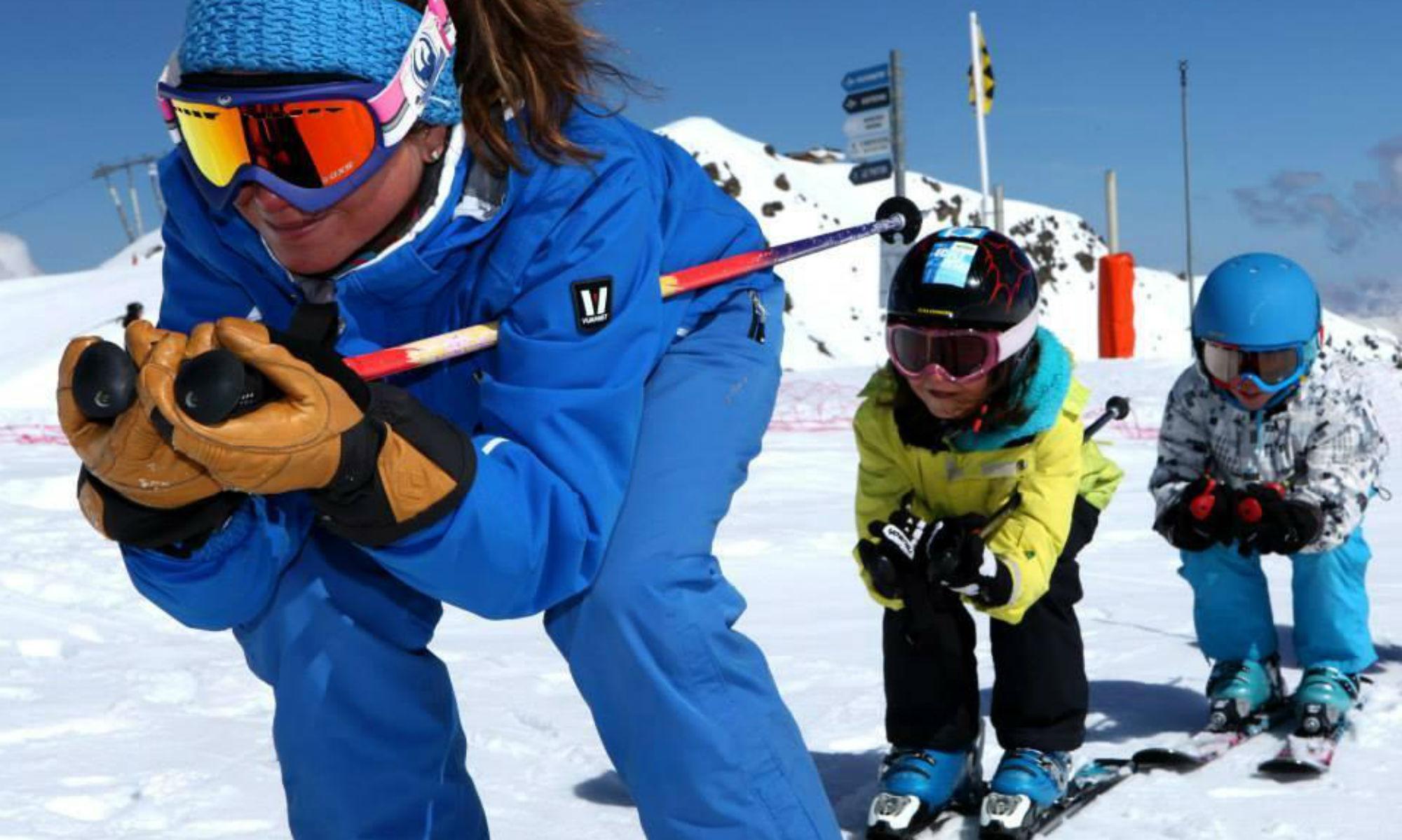Die Skilehrerin und 3 Kinder stehen vor dem Bergpanorama des Skigebiets Les 3 Vallées und grinsen in die Kamera.