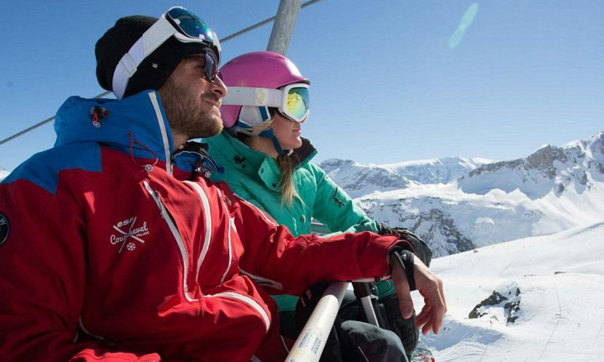A private ski instructor and a female skier are sitting on a chairlift and enjoying the view over the ski resort of Courchevel.