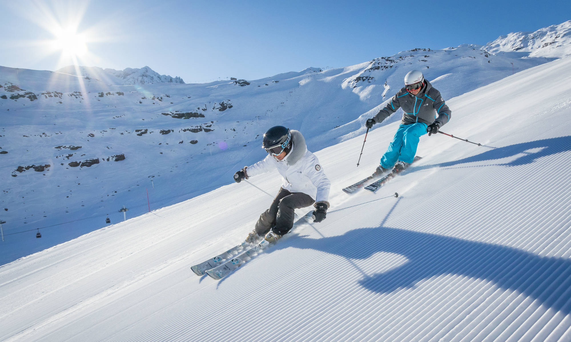 Two skiers are skiing on a freshly groomed piste in front of the mountain panorama of Val Thorens.