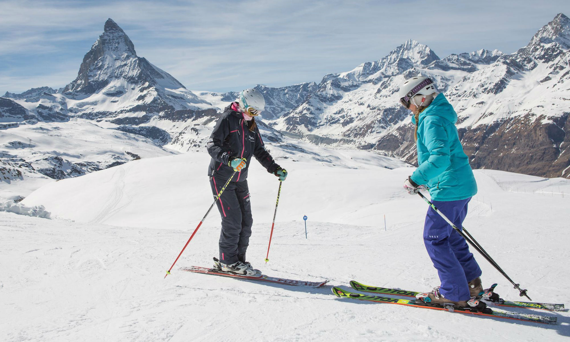 A ski instructor and a skier are standing on the piste in front of the Matterhorn in Zermatt.