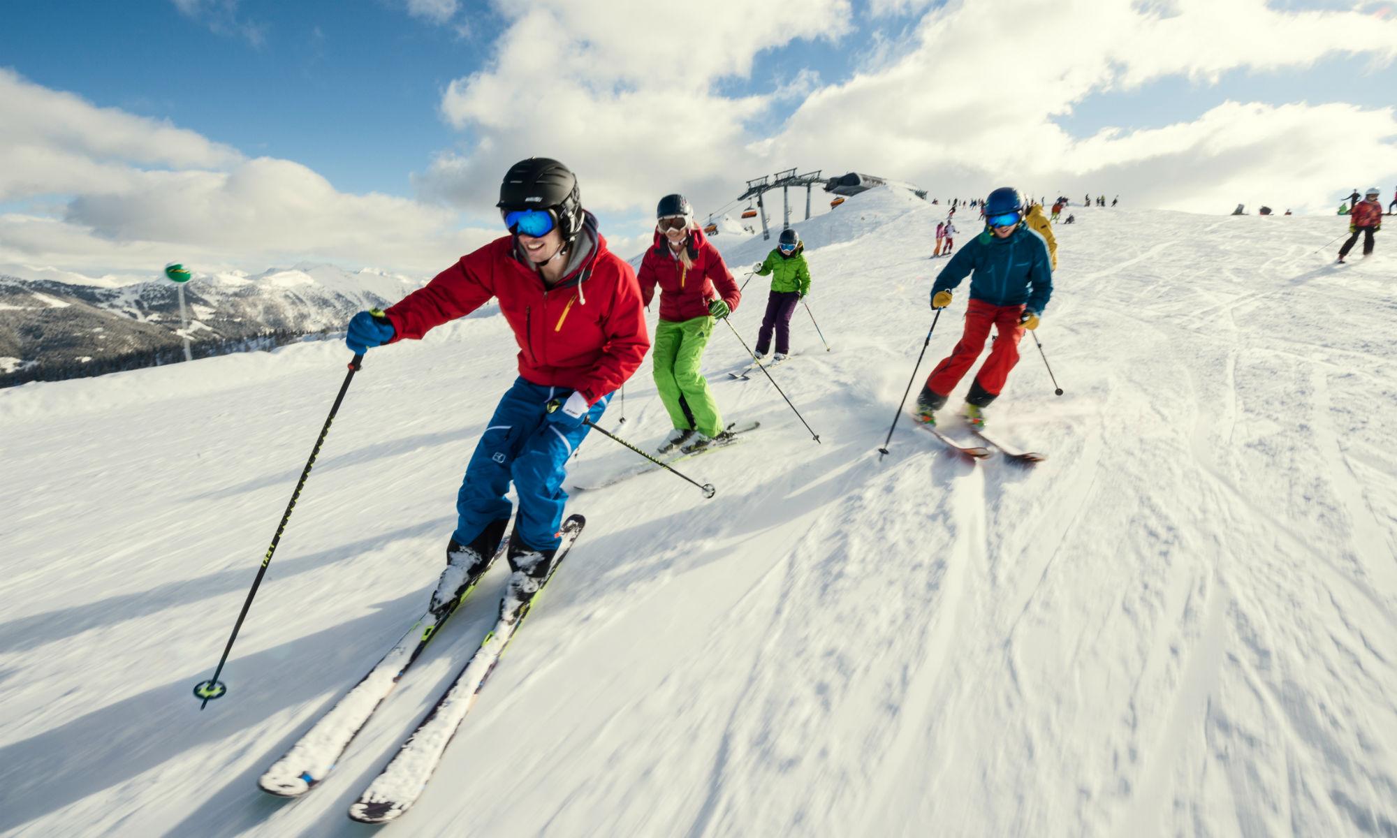 4 Skifahrer fahren gemeinsam auf einer sonnigen Piste in Flachau Ski.