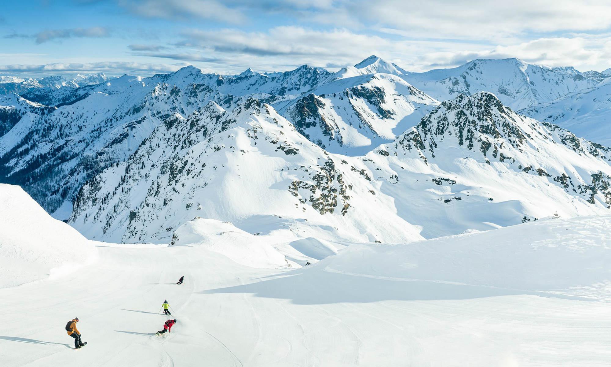 4 Wintersportler fahren auf einer von verschneiten Bergen umgebenen Piste in Obertauern.