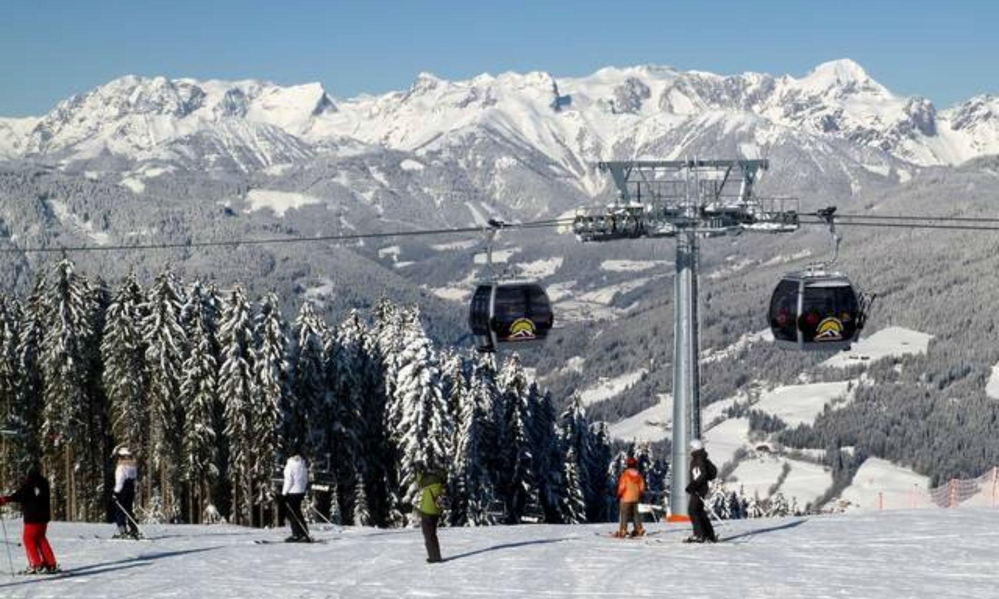 6 Skifahrer auf einer Piste mit Gondel und Bergpanorama in Radstadt-Altenmarkt.