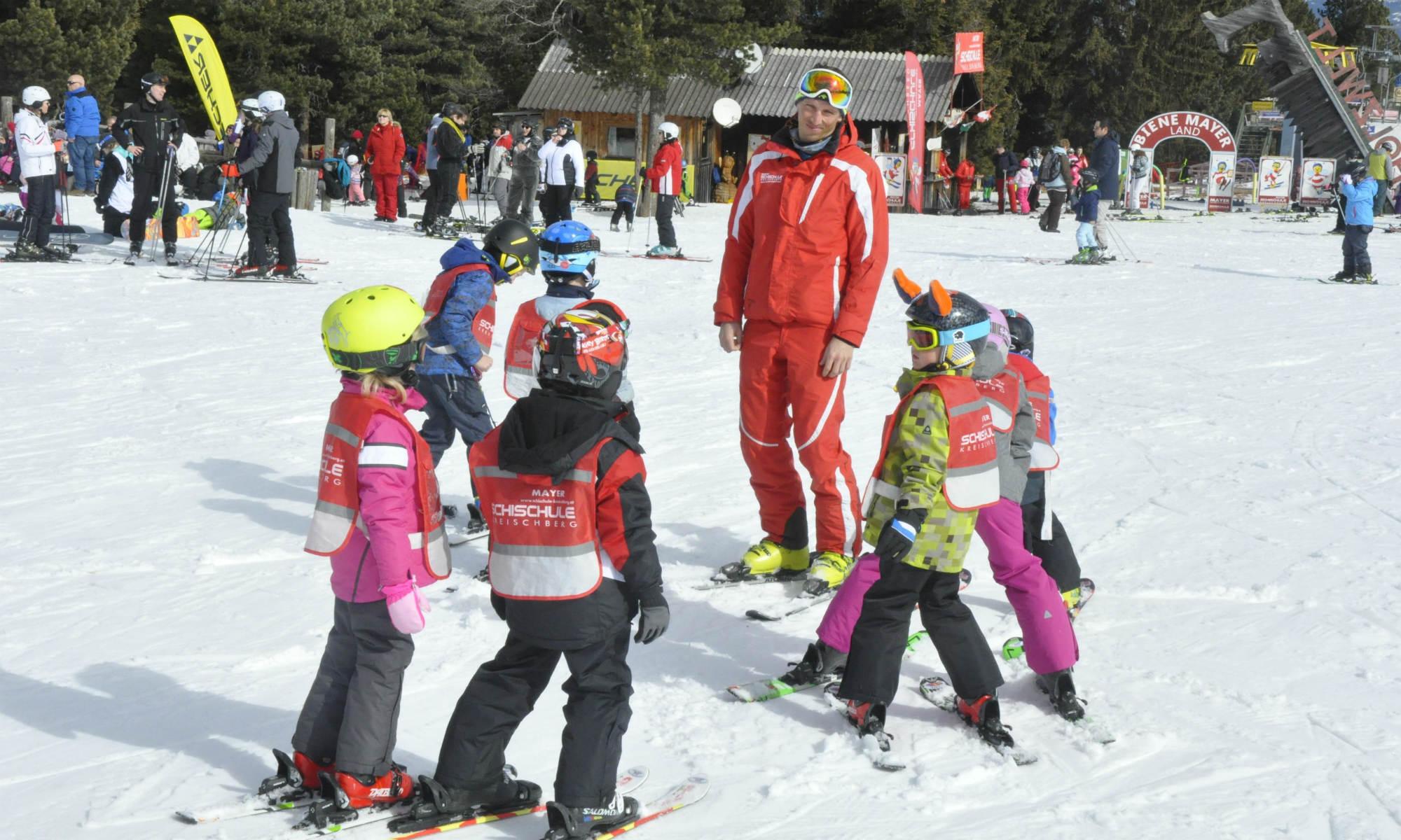 Ein Skilehrer gibt 7 Kindern Skiunterricht am Kreischberg.