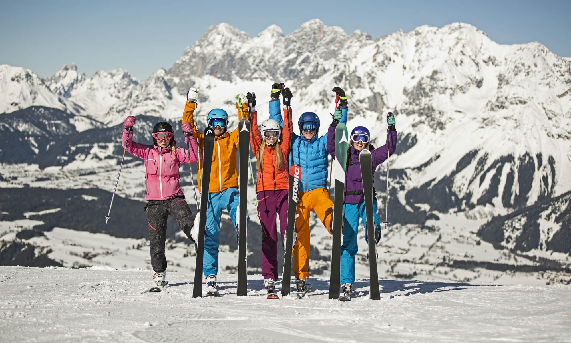 5 Skifahrer mit aufgestellten Skiern vor dem Panorama des Skigebiets Schladming Planai.
