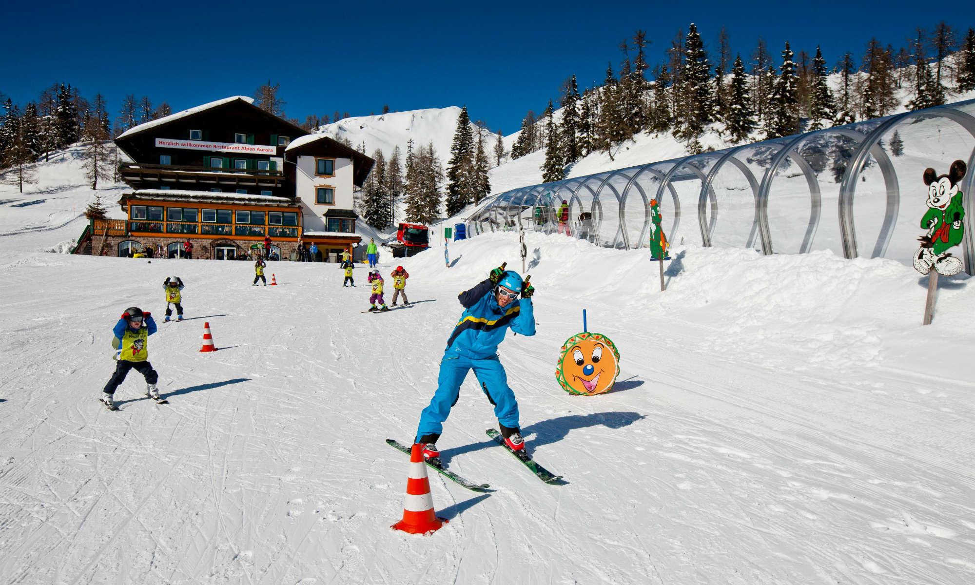 Ein Skilehrer und Kinder beim Skikurs im Kinderland auf der Tauplitzalm.