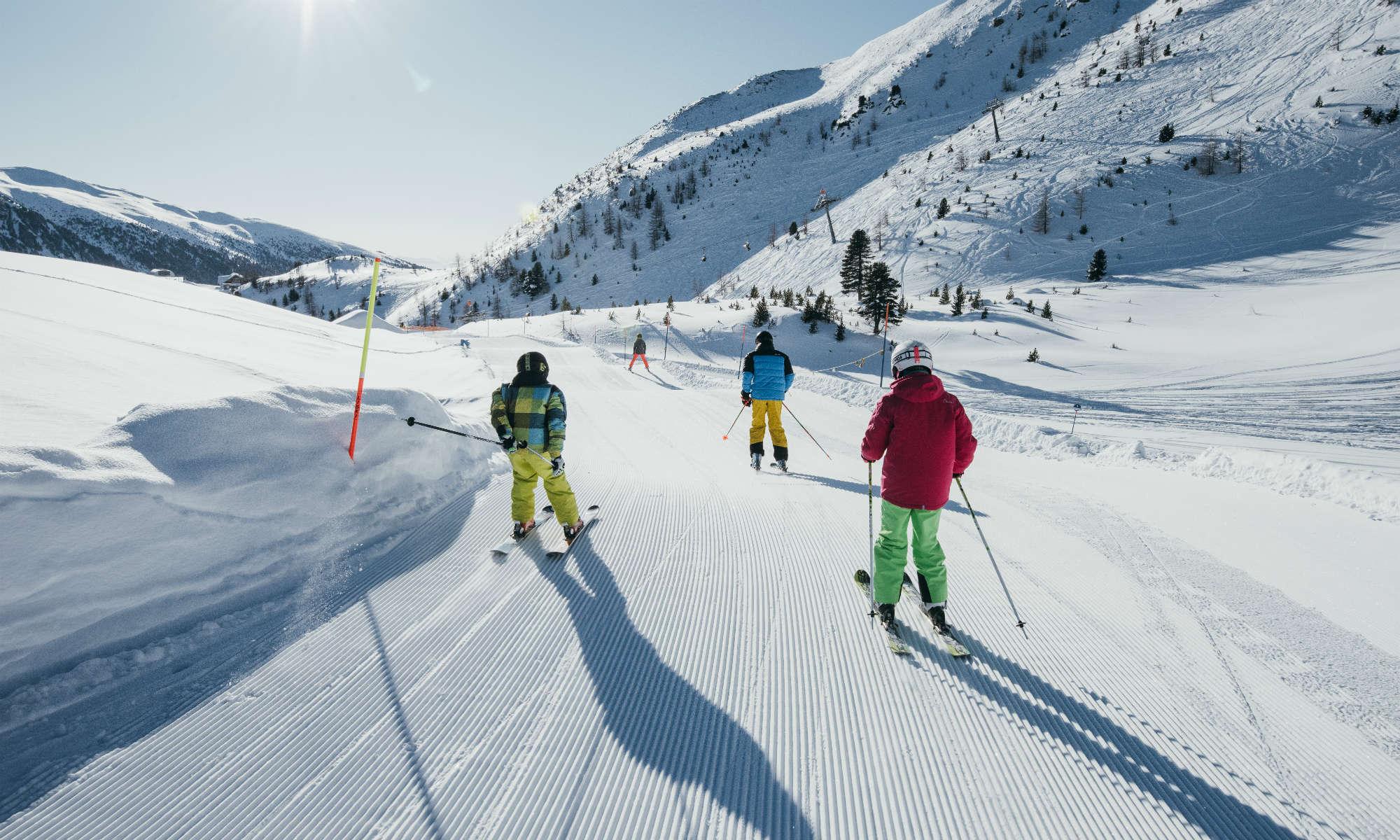 Eine Familie beim Skifahren auf der Funslope im Skigebiet Turracher Höhe.