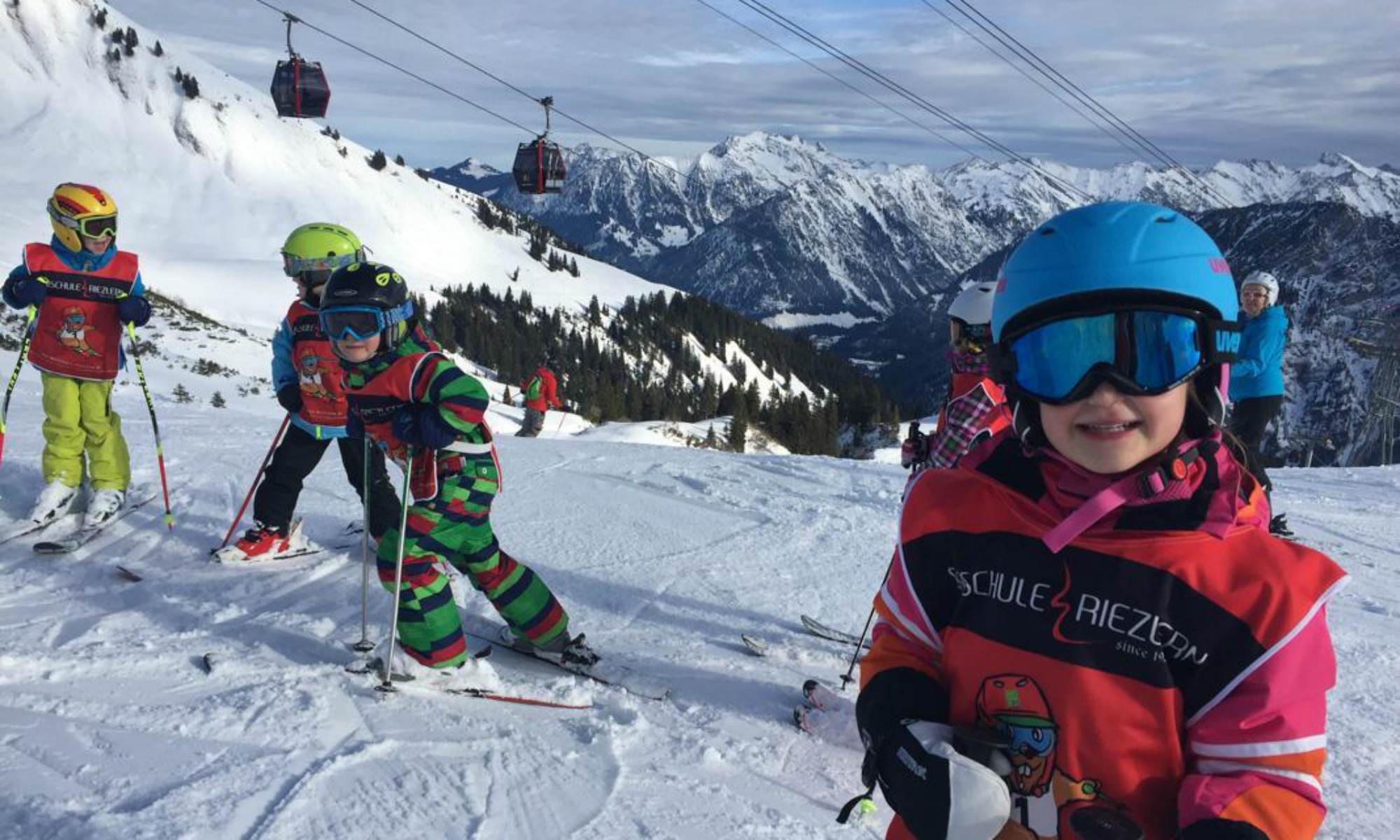 Kinder beim Skikurs auf einer Piste im Skigebiet Kleinwalsertal.