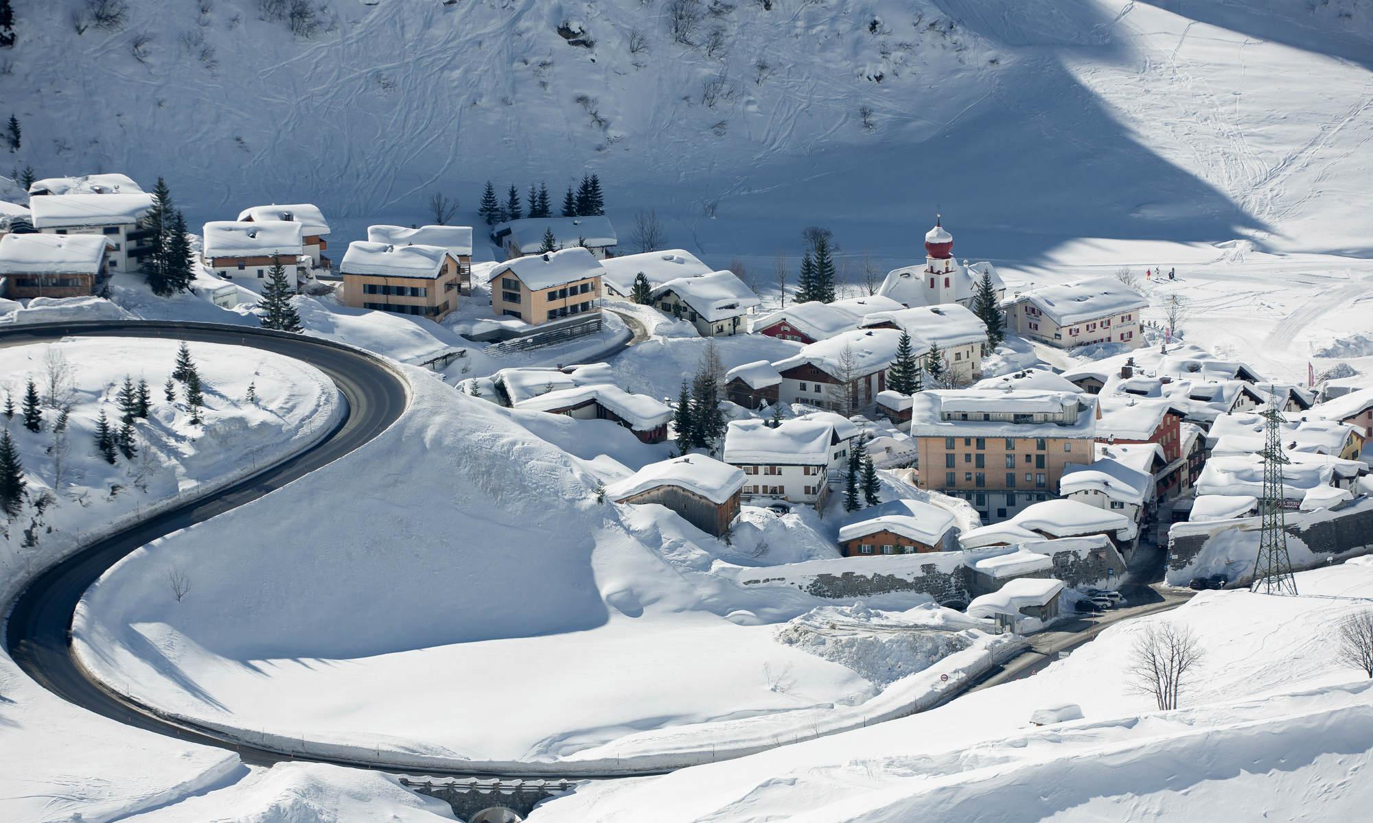 Ein Blick von oben auf das tief verschneite Bergdorf Stuben am Arlberg.