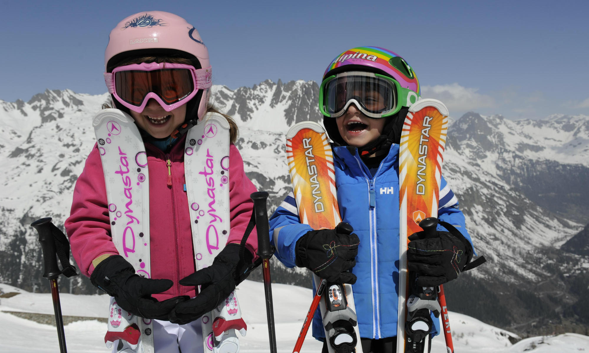 2 glückliche Kinder mit Skiern vor der traumhaften Bergkulisse in Warth.