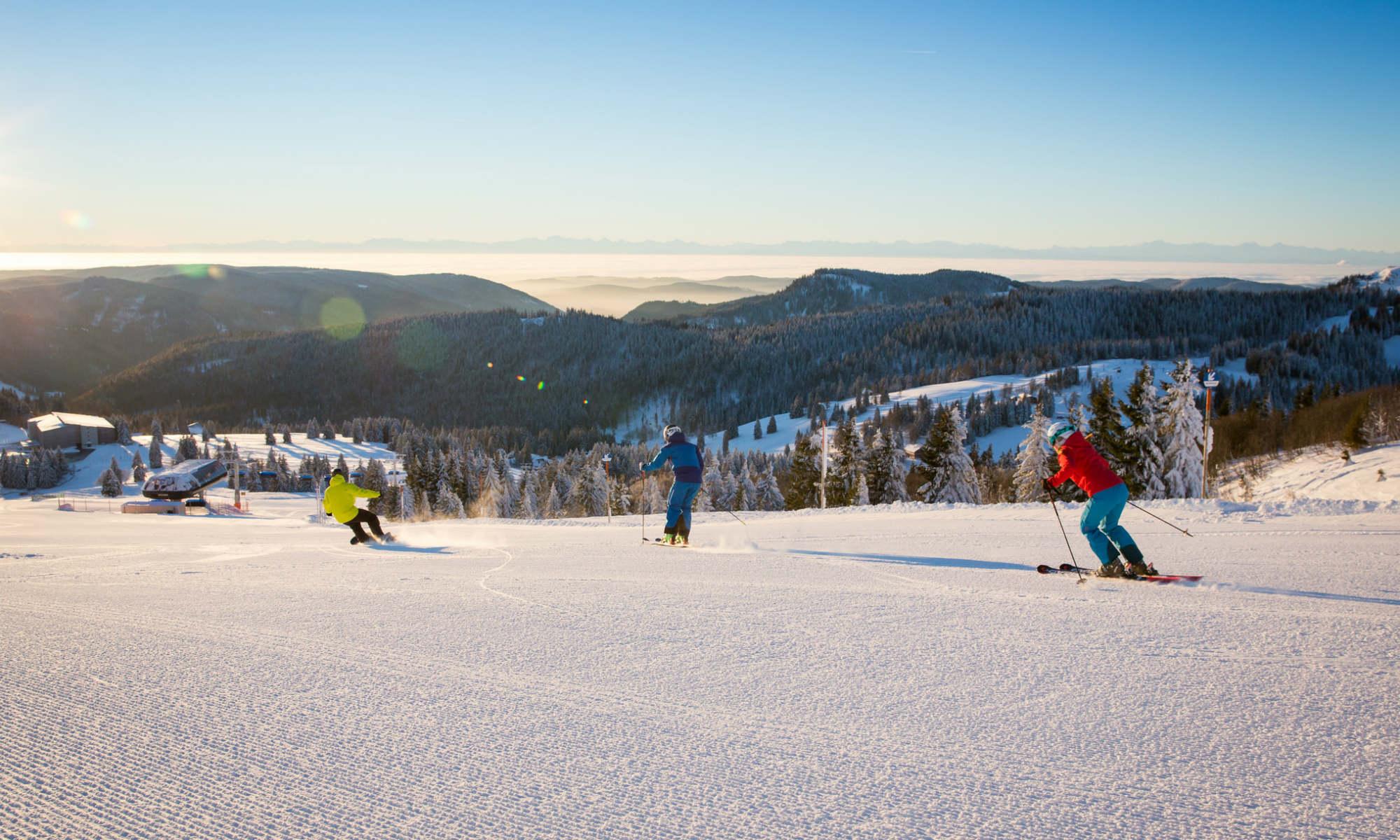 2 Skifahrer und 1 Snowboarder auf einer einfachen Piste im Skigebiet Feldberg.
