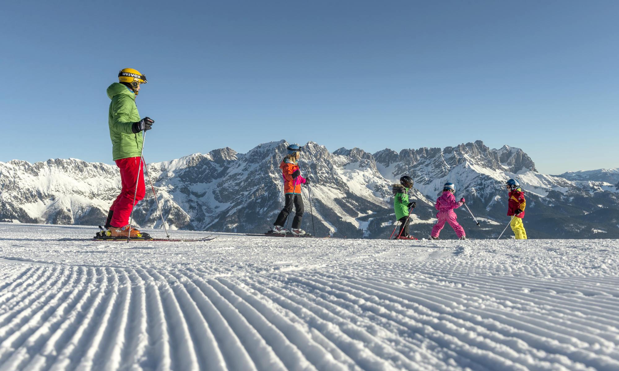 2 Erwachsene und 3 Kinder beim Skifahren in Going-Ellmau vor einer wunderschönen Bergkulisse.