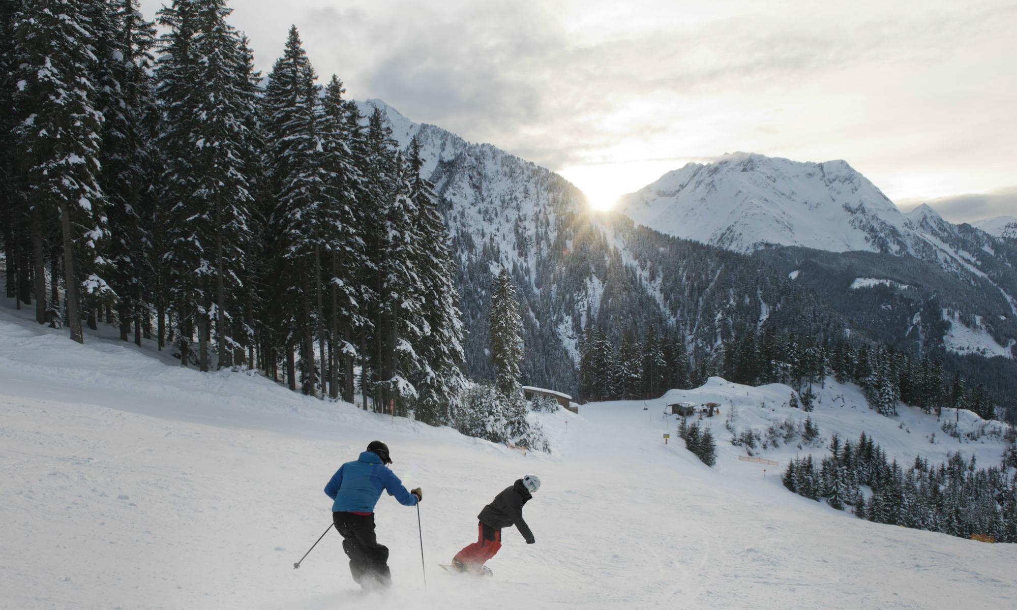 Ein Skifahrer und ein Snowboarder fahren die Piste in Mayrhofen hinunter.