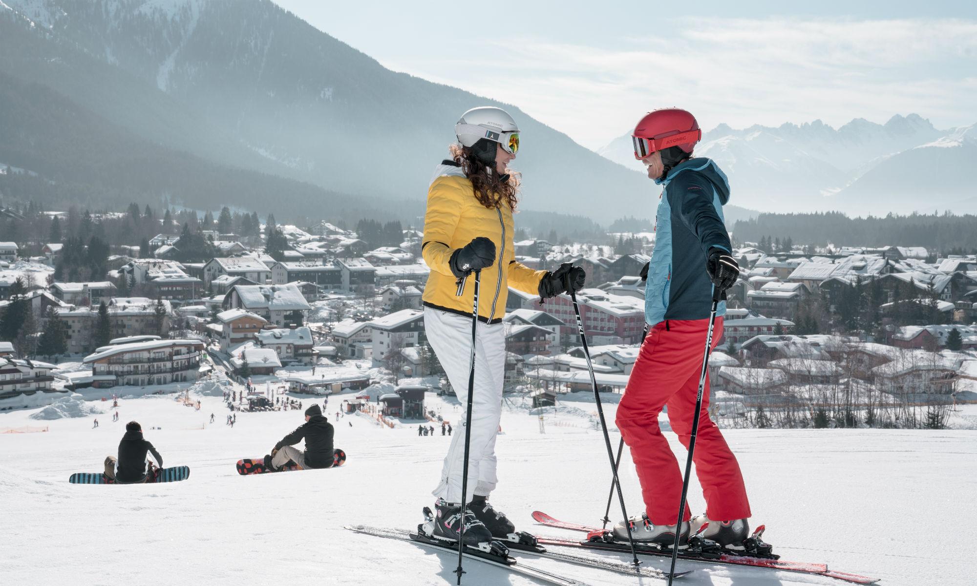 2 Skifahrer unterhalten sich auf einer einfachen Skipiste im Skigebiet Seefeld.