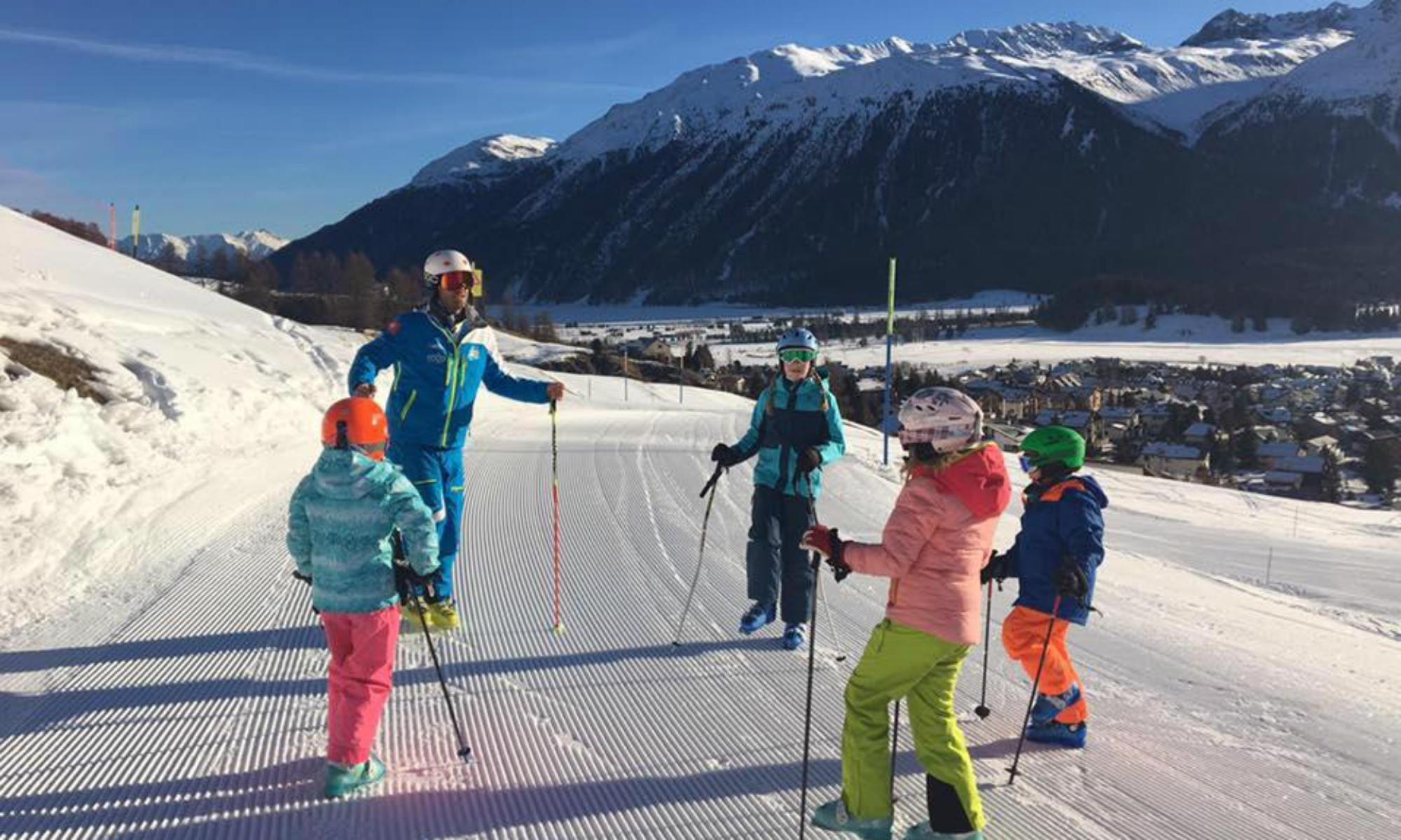Ein Skilehrer macht mit einer Gruppe Kinder Aufwärmübungen auf der Piste.