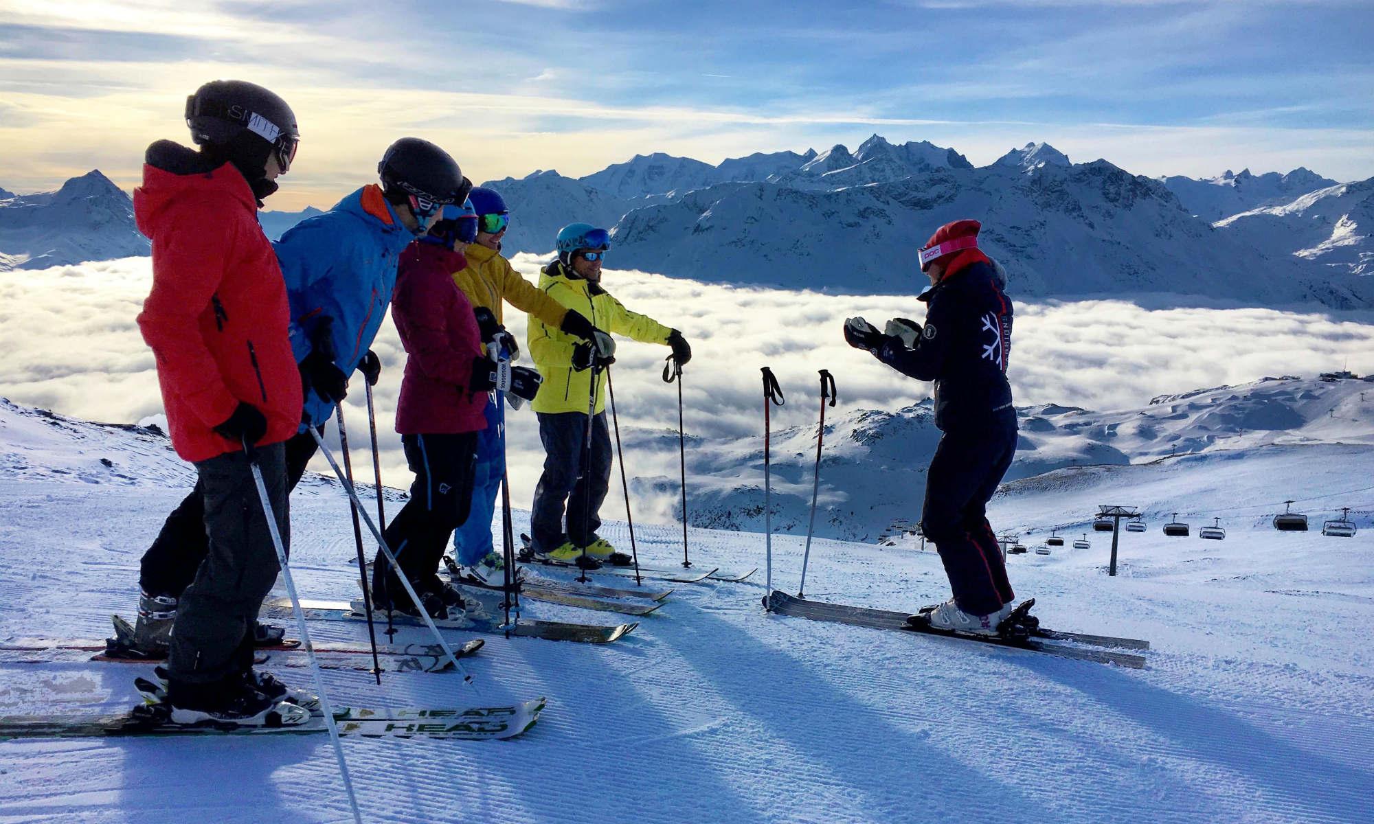 Ein Skilehrer steht mit einer Gruppe von Skifahrern am Rand der Piste.