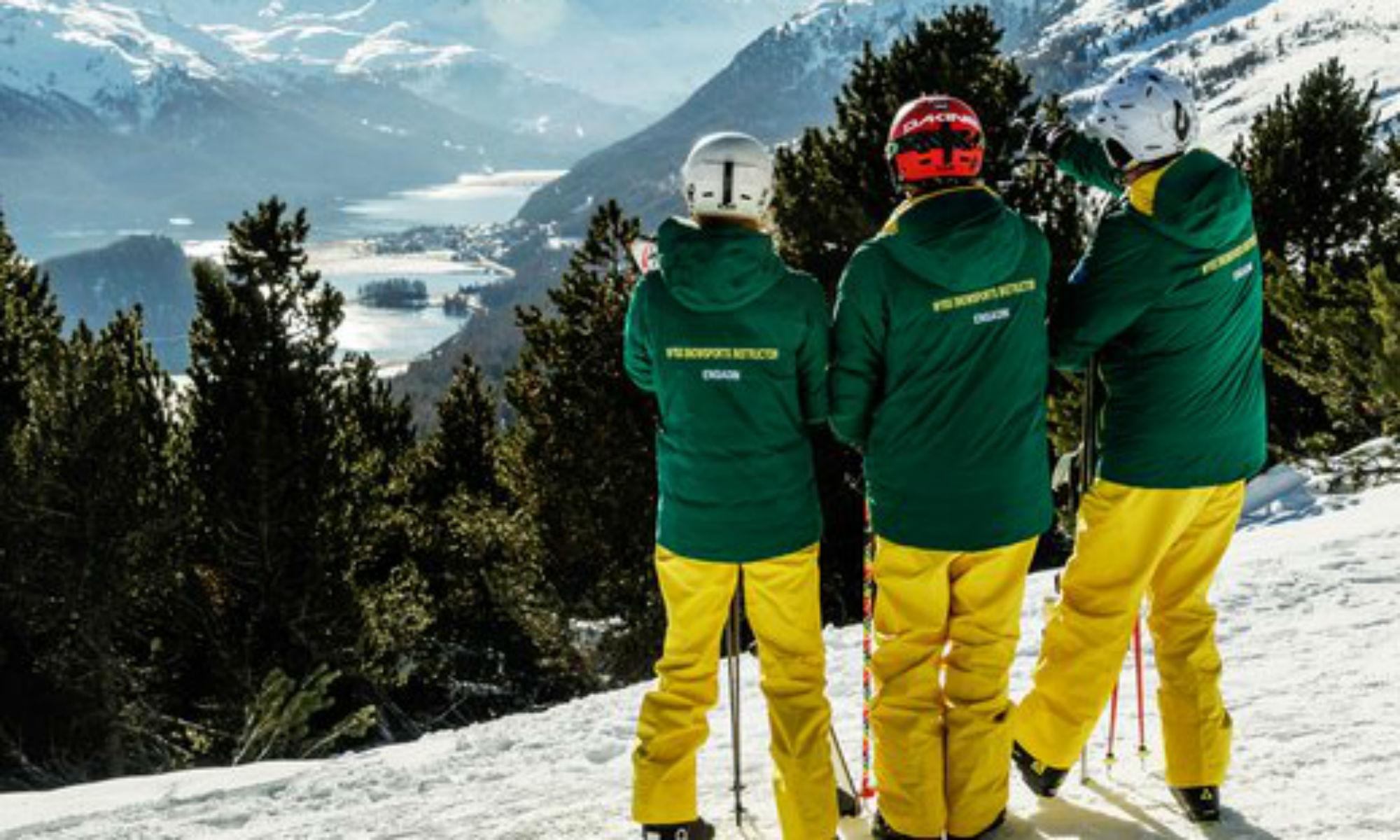 3 Skilehrer der Skischule Wyss Snowsports blicken vom Berg hinab in das Tal.