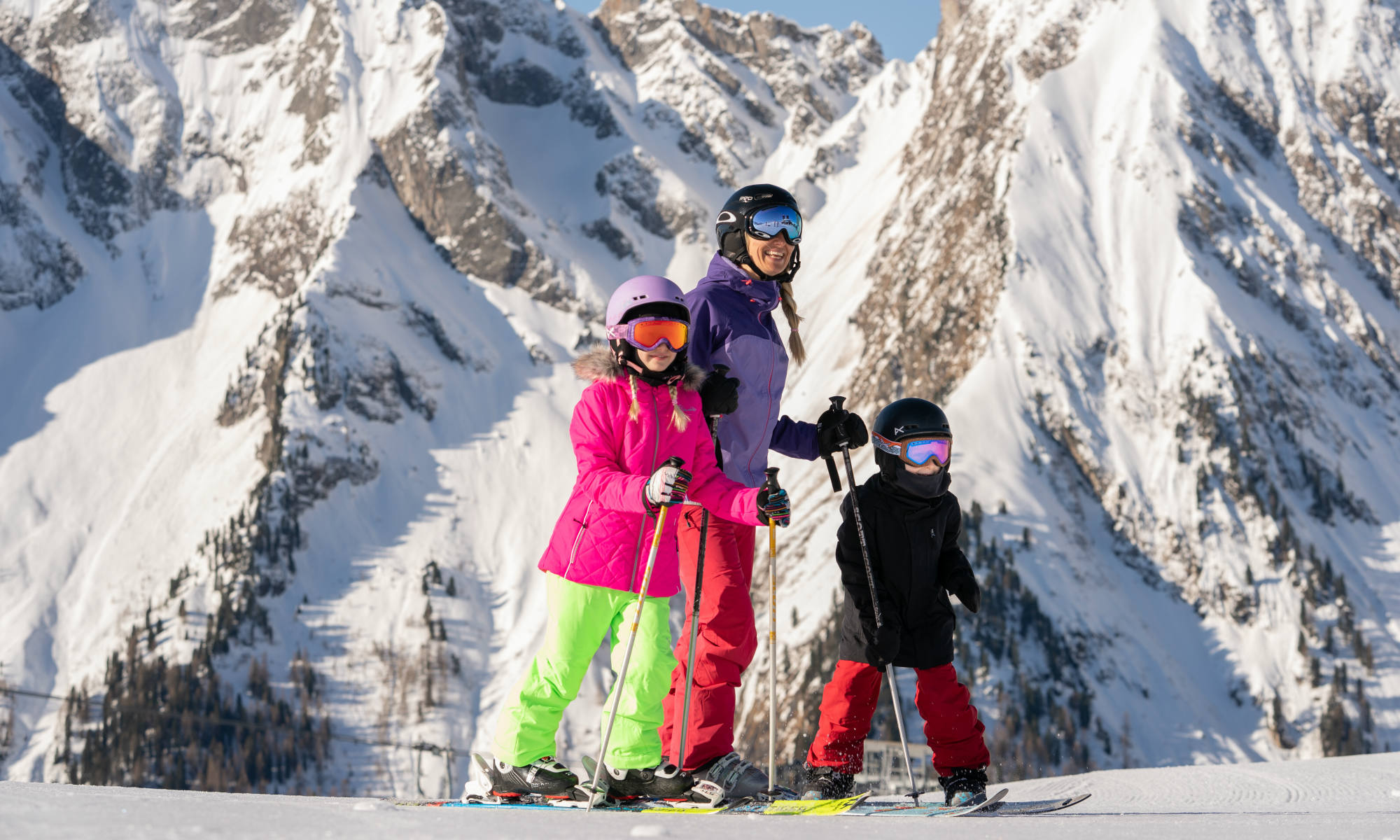A mother with her kids standing on a sunny slope in Mayrhofen.