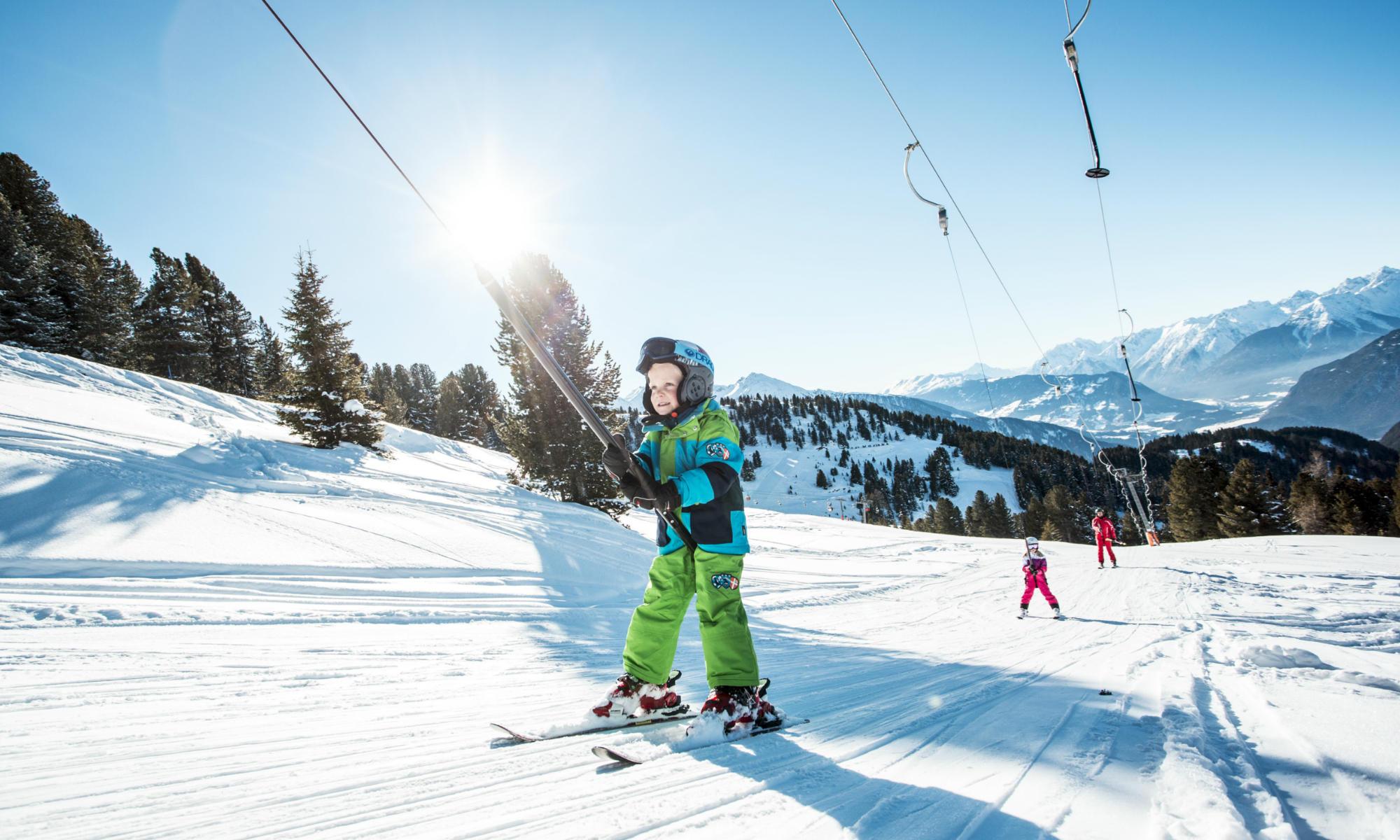 Boy taking the drag lift to the mountain station of the ski resort Sölden.