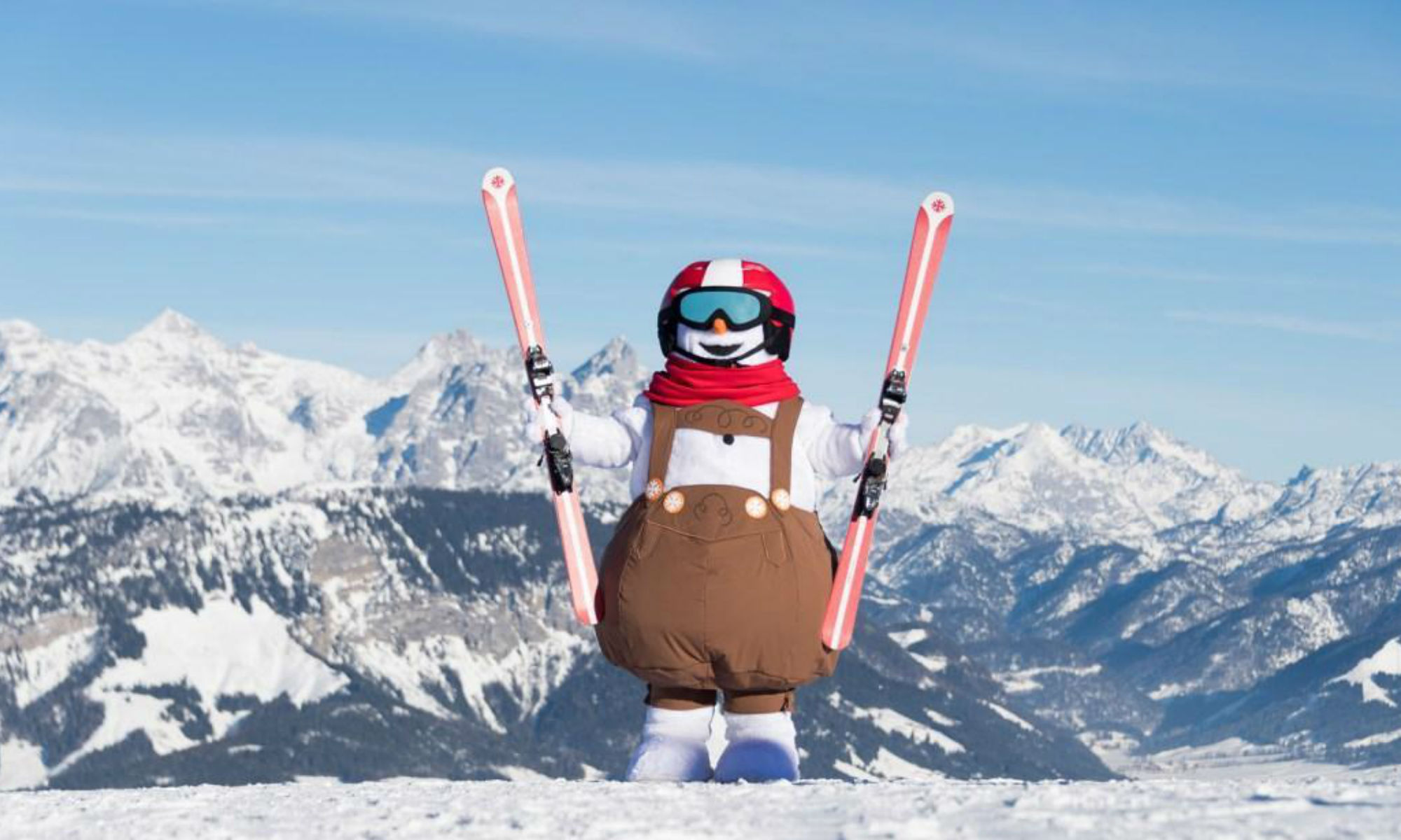 The mascot Valle standing on the piste with the mountain scenery of St. Johann in Tirol in the background.