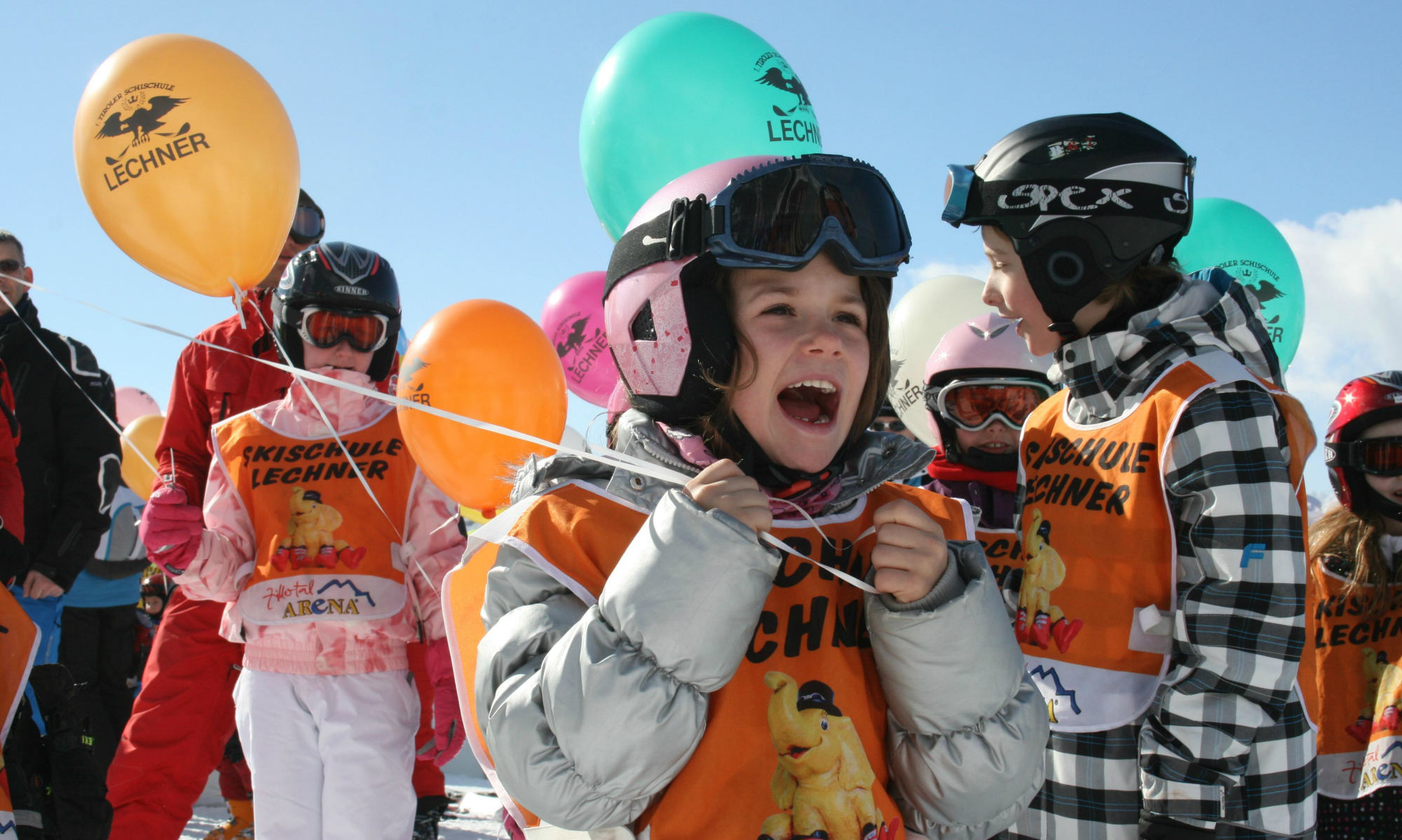 Children in the kid's area ArenaFuntenland in Zell am Ziller, holding balloons in their hands.