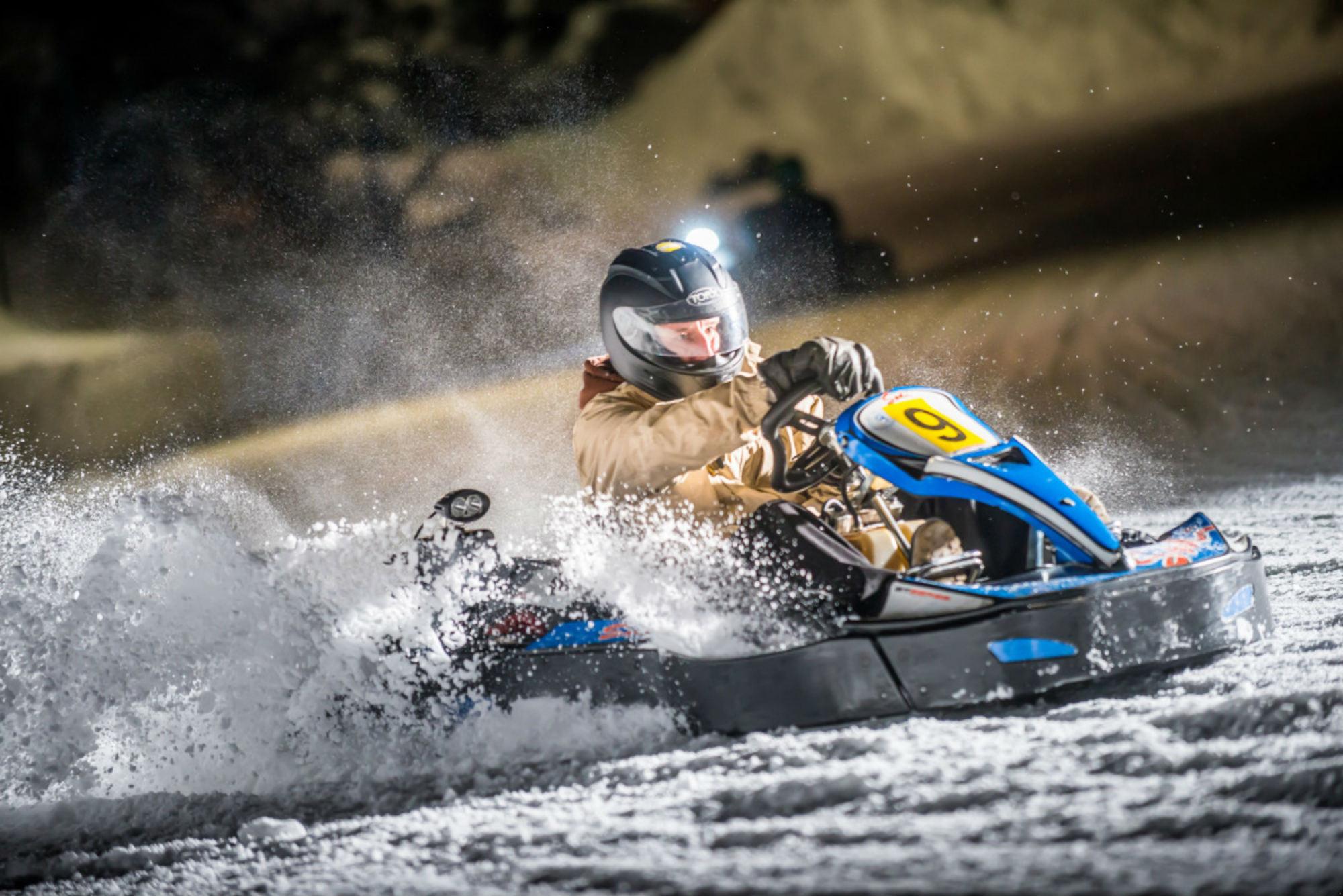 Un pilote de kart sur une piste de karting enneigée.