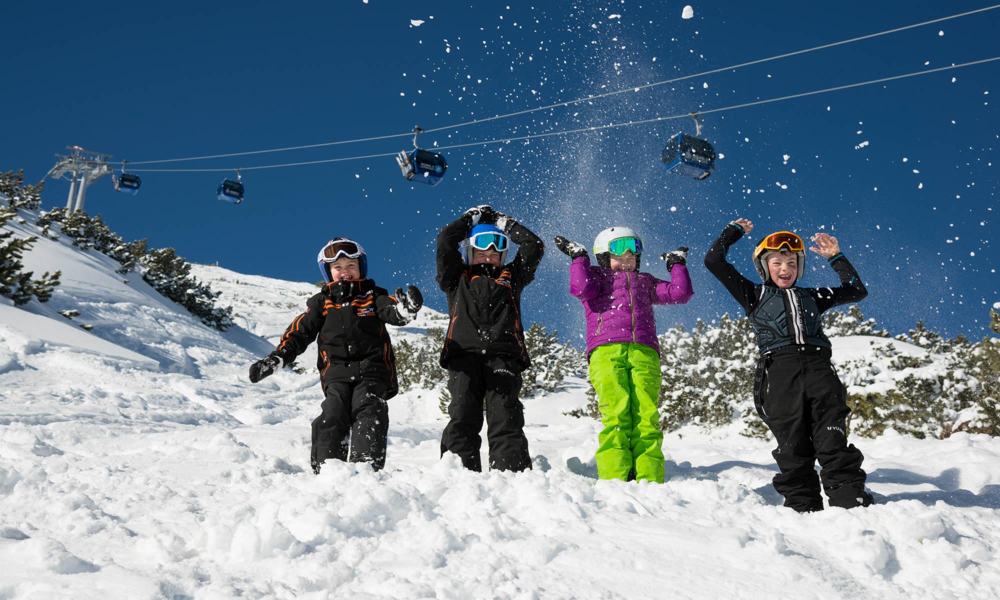 4 kinderen spelen in de sneeuw van Lermoos met de skilift op de achtergrond.