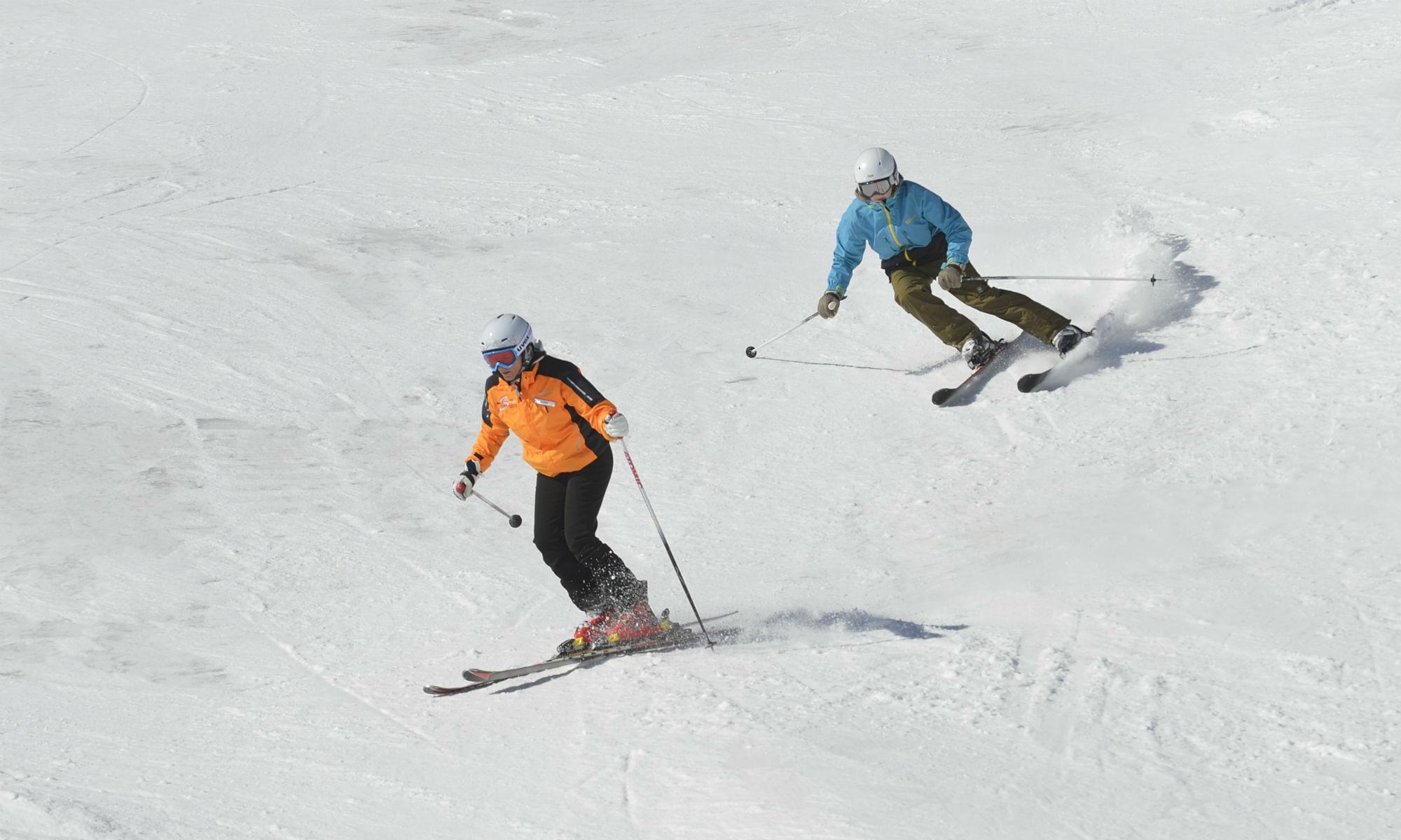 Ein Skifahrer überholt eine Skifahrerin auf der Piste.