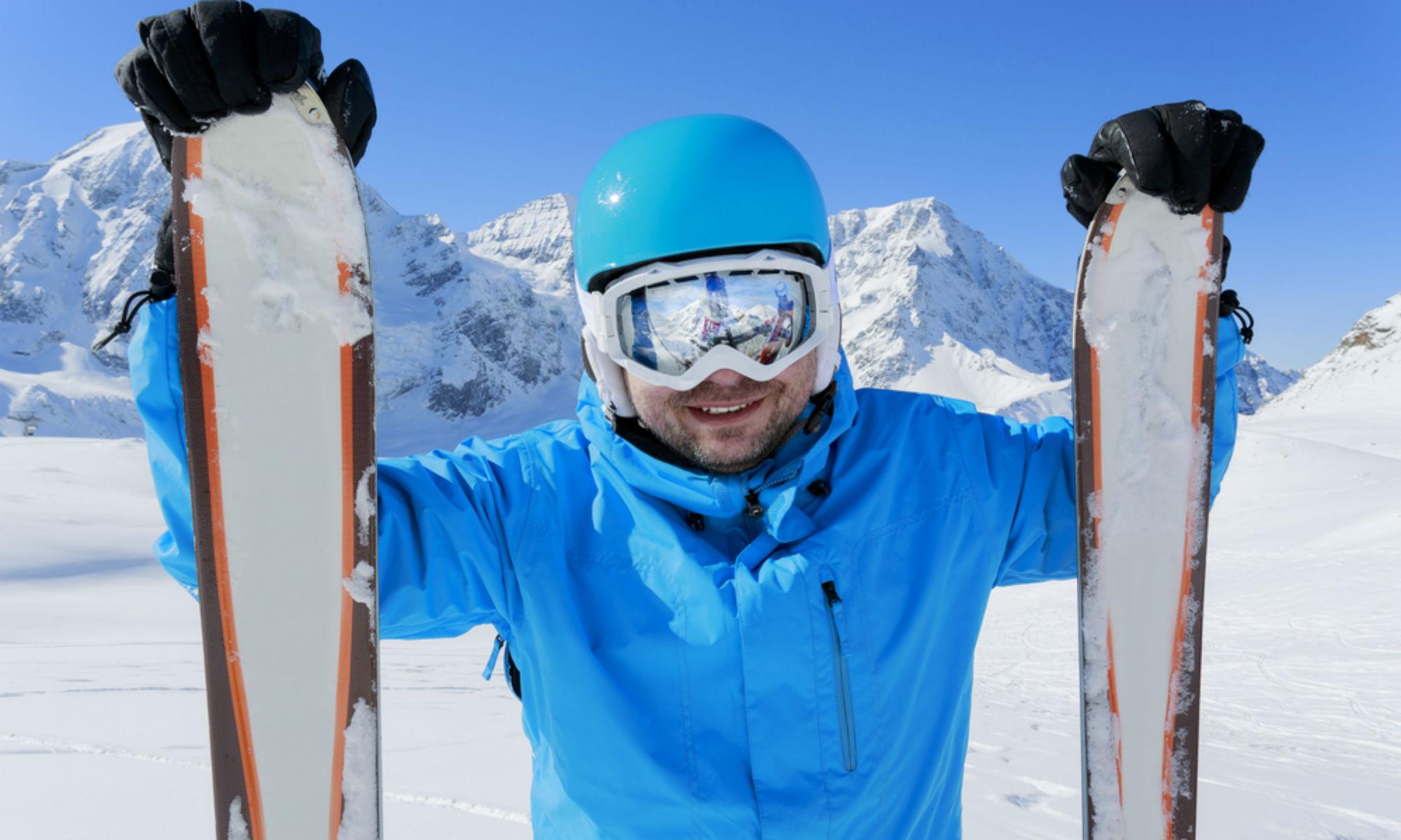 Skifahrer mit Helm und Skiern lächelt in die Kamera.