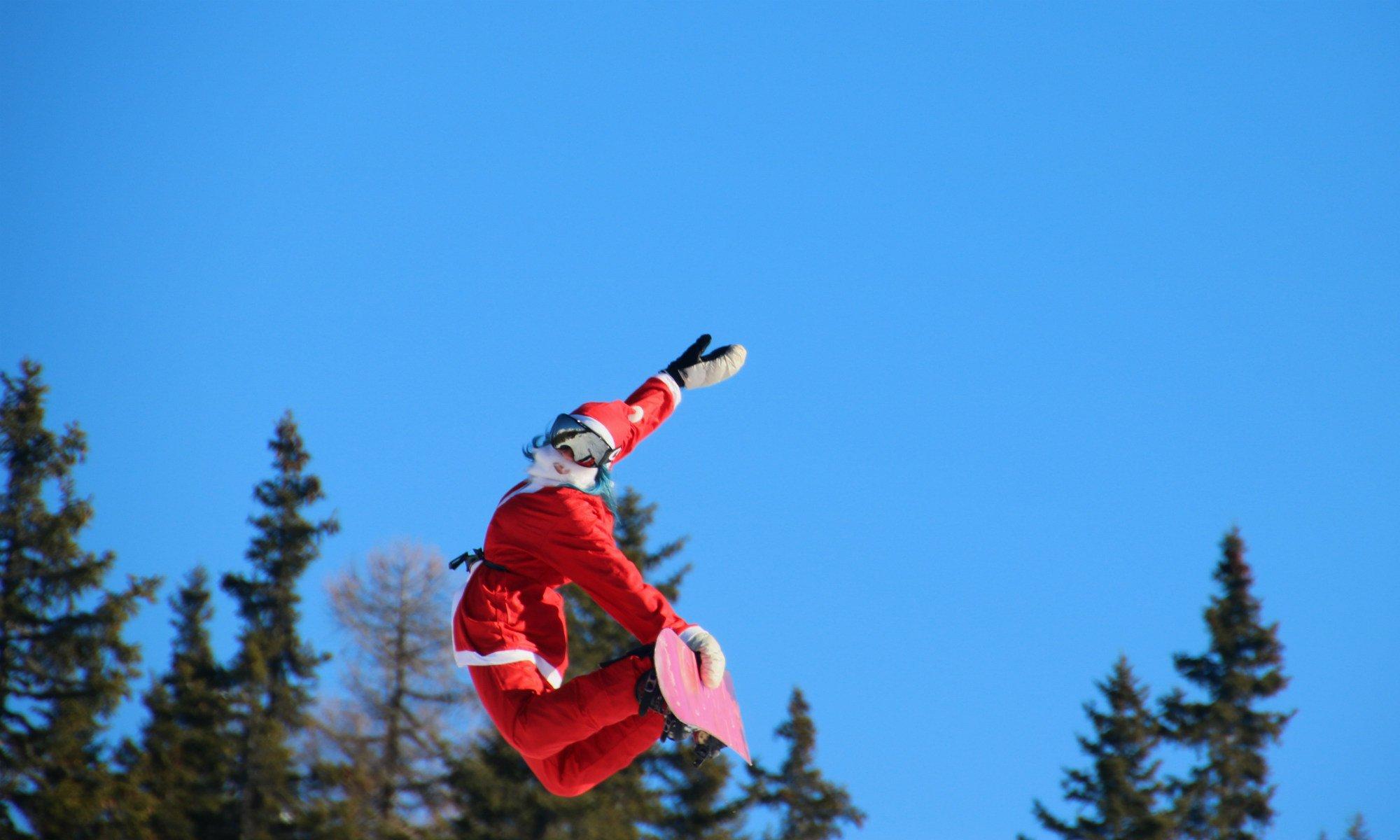 Un maestro di snowboard in Val Malenco vestito da Babbo Natale.