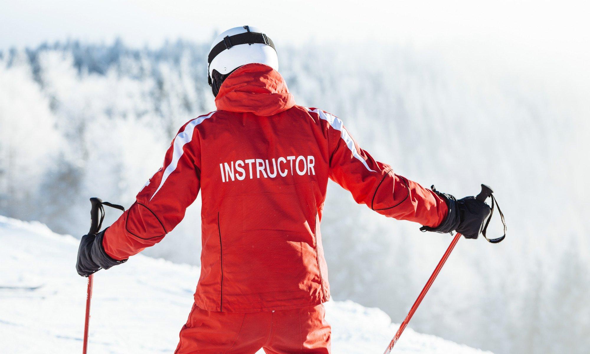 Un moniteur de ski est de dos sur une piste enneigée.