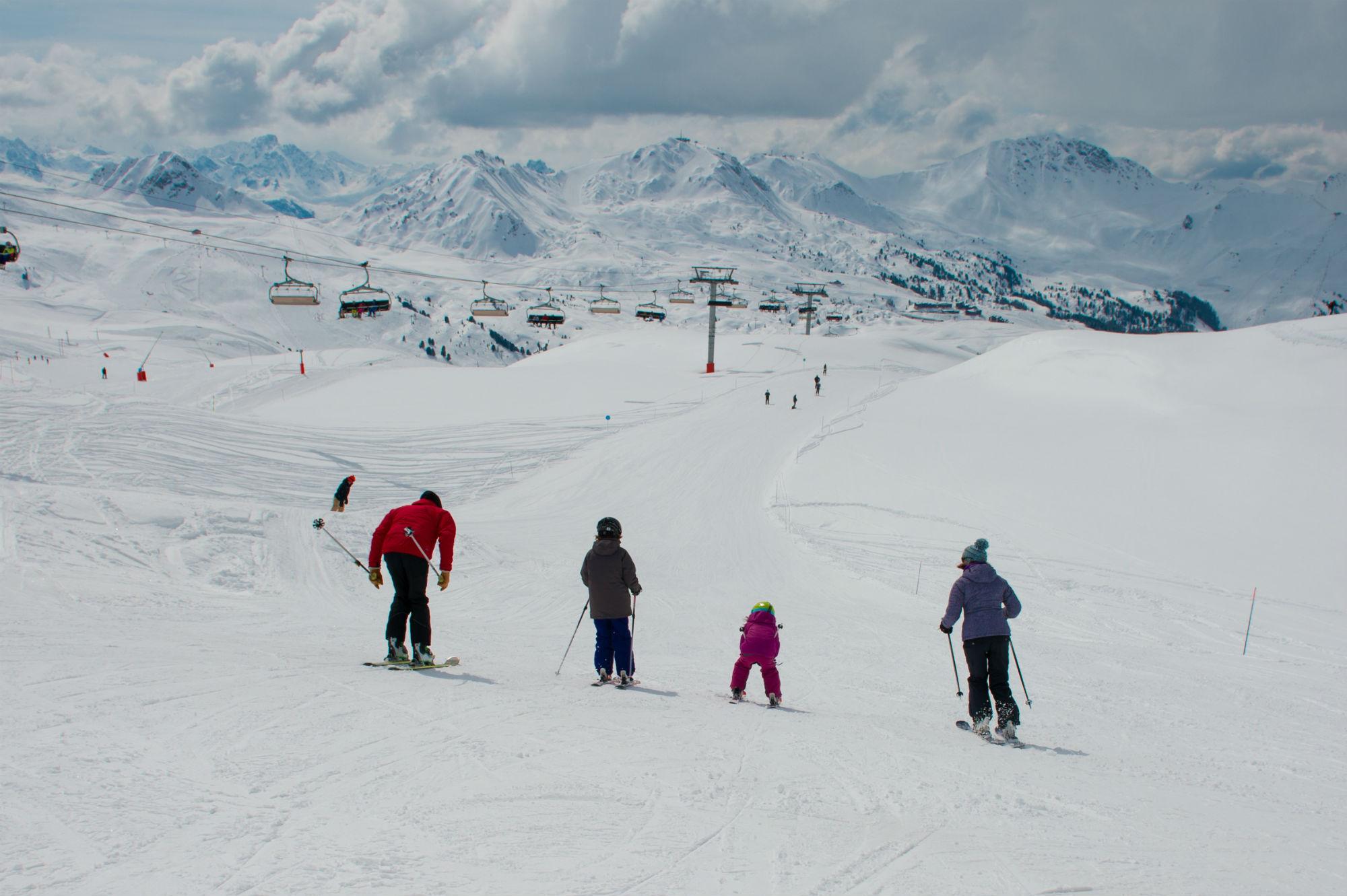 Une famille sur une piste de ski enneigée à La Plagne.