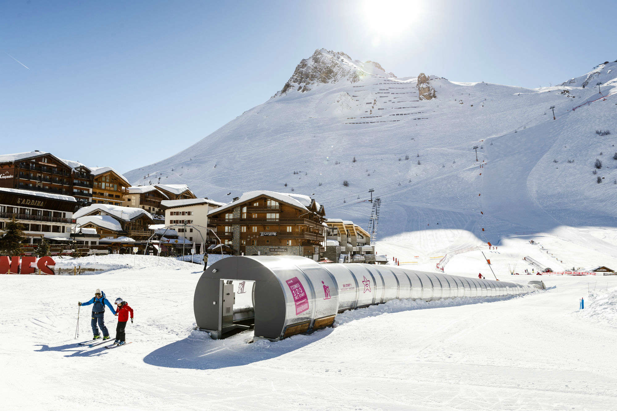 Deux skieurs devant un tapis roulant dans une zone débutants à Tignes.