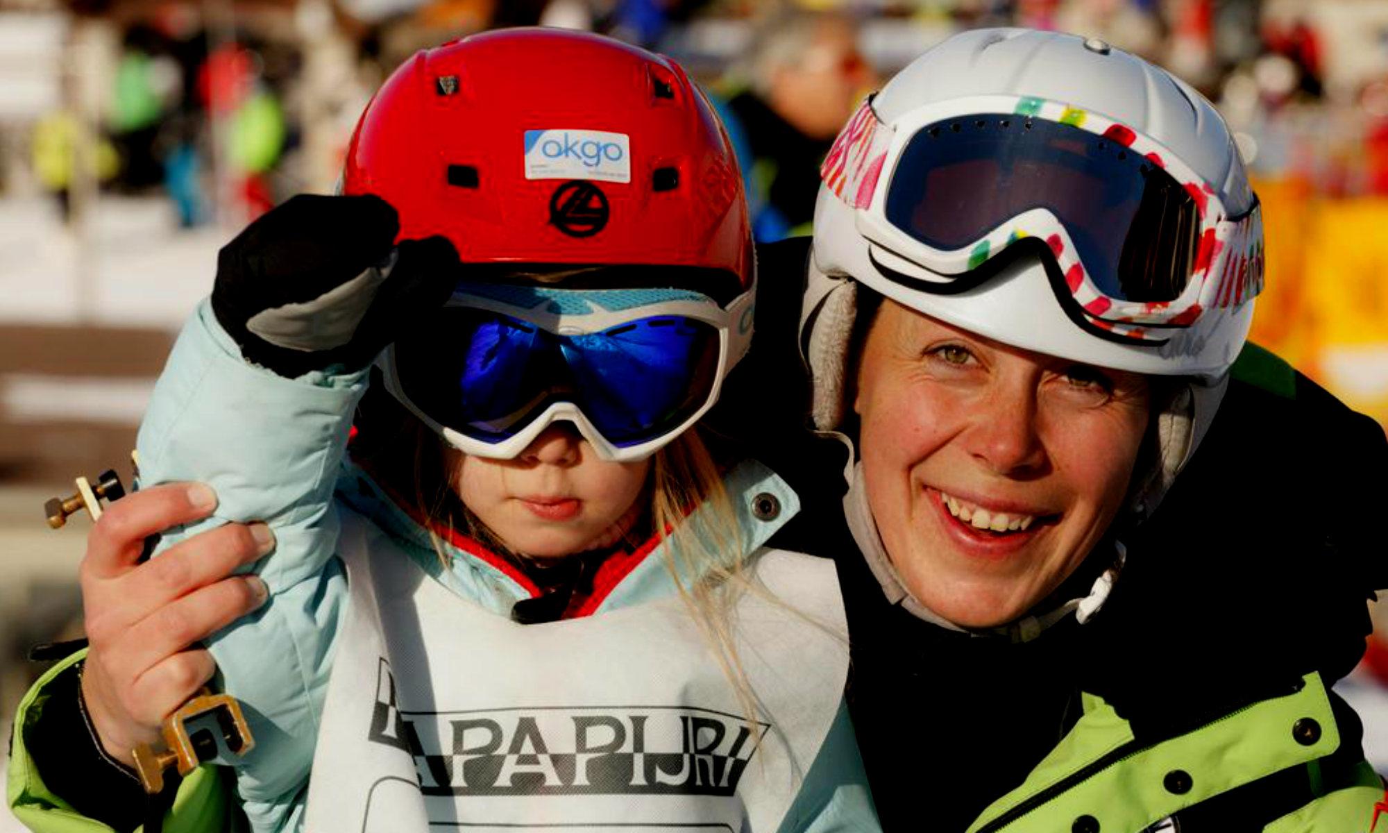 Una maestra di sci è pronta per iniziare la lezione di sci insieme a una bambina.