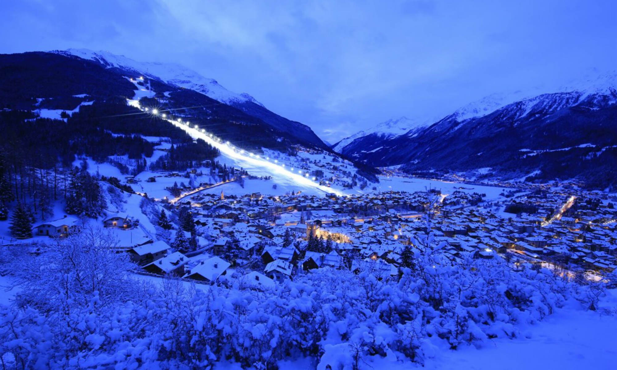 Montagne imbiancate e case illuminate, il panorama bellissimo di Bormio.