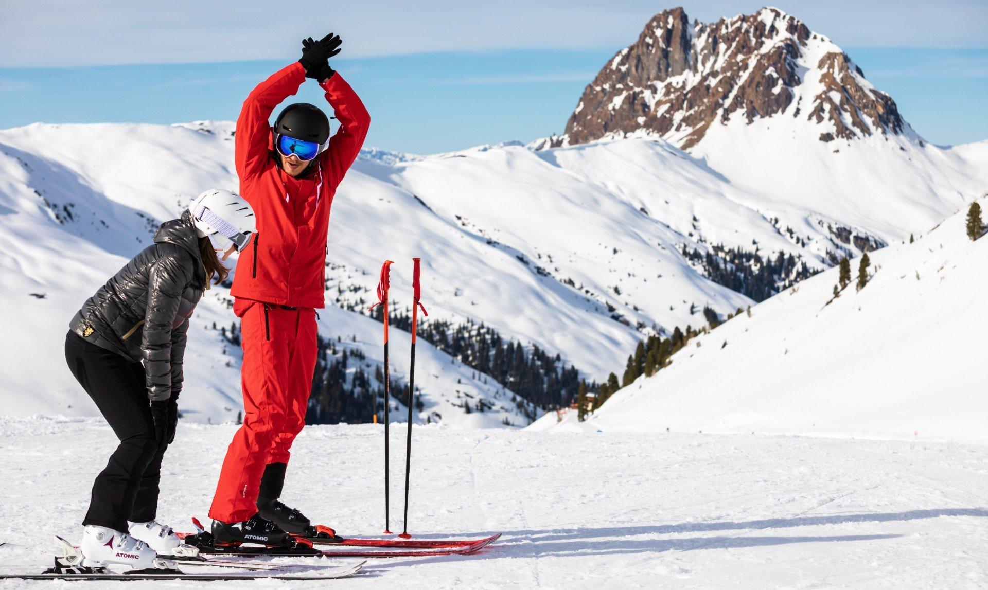 Ein Skilehrer und ein Mädchen wärmen sich vor dem Skiunterricht auf.