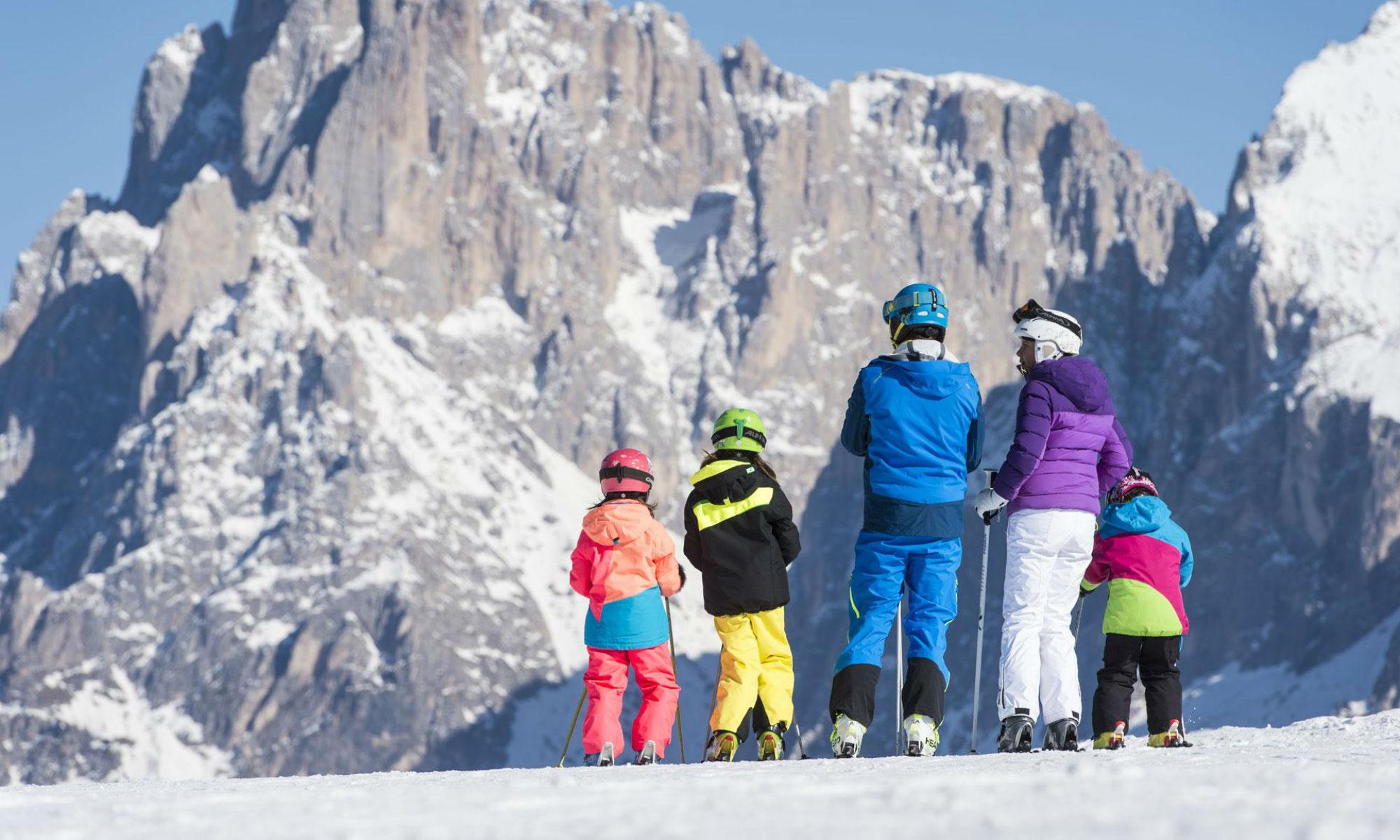 Erwachsene und Kinder genießen das Bergpanorama auf den Skipisten in Gröden.